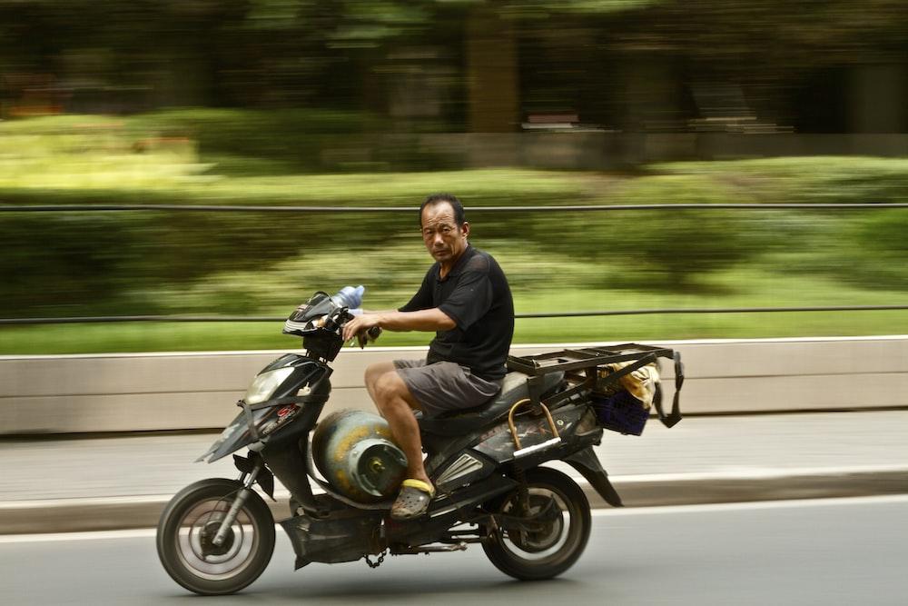 photo of man wearing black shirt riding motorcycle