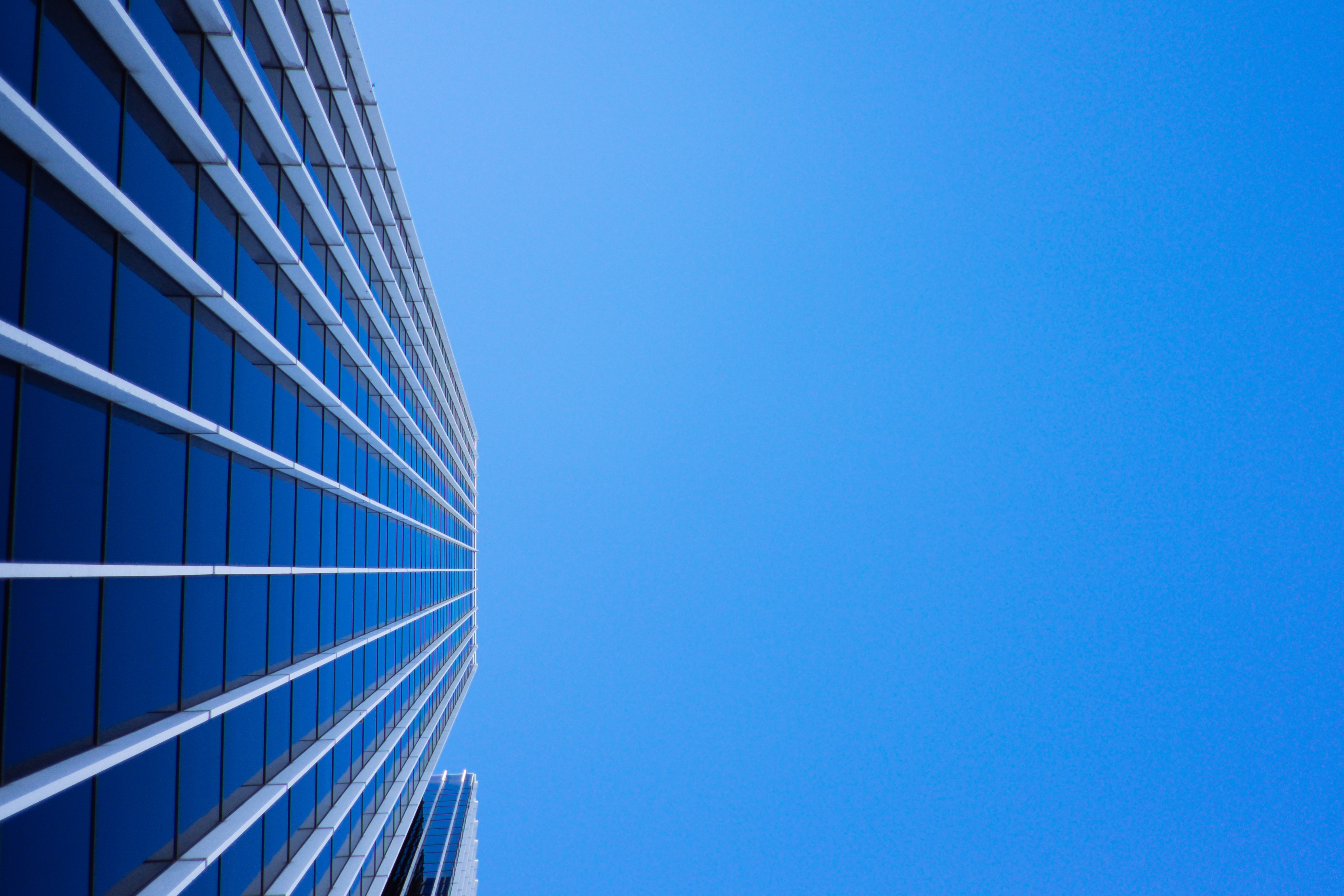 low-angle photography of curtain glass building under blue sky