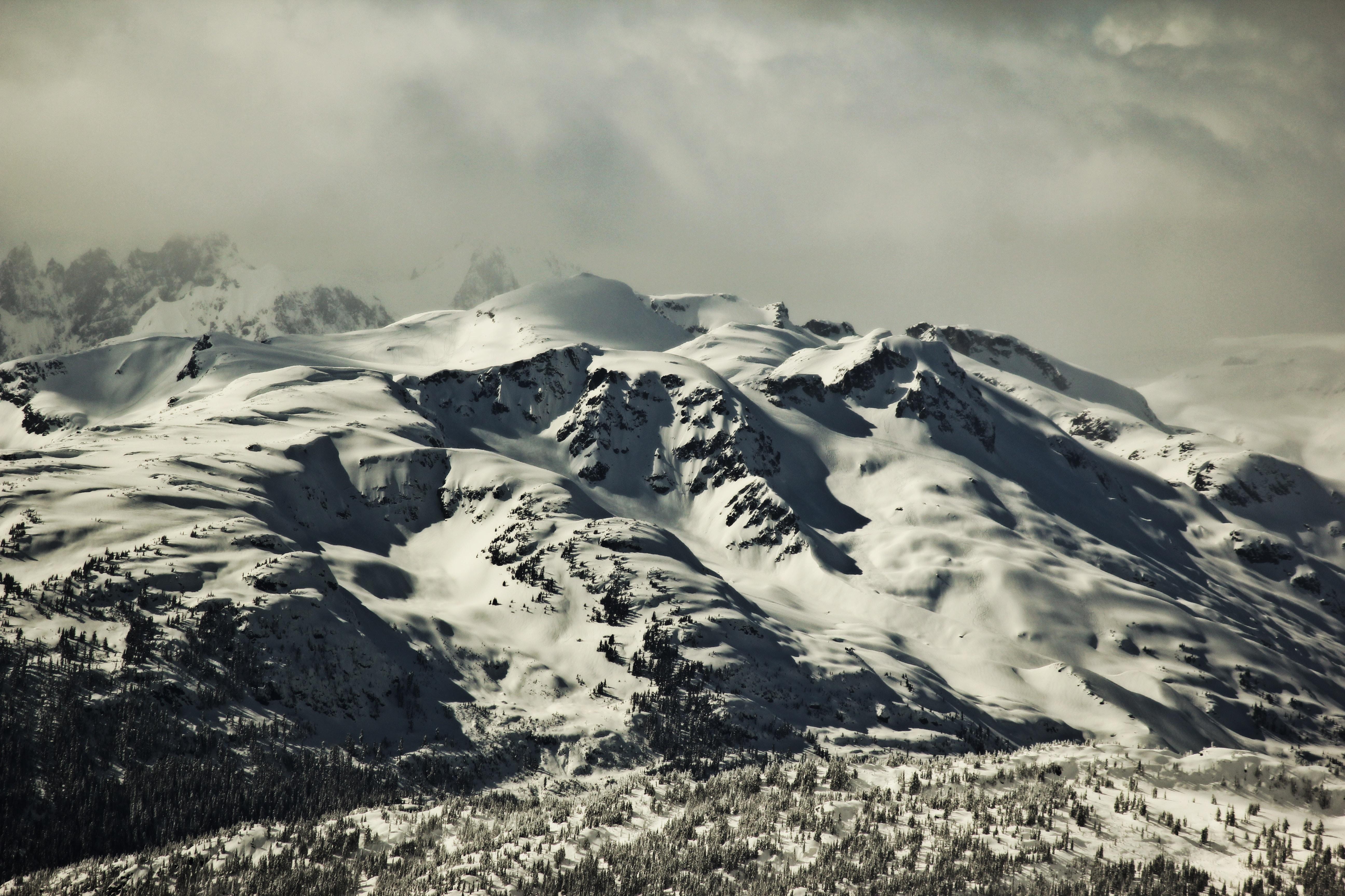 Snow on a mountain range with a cloudy sky on an overcast day