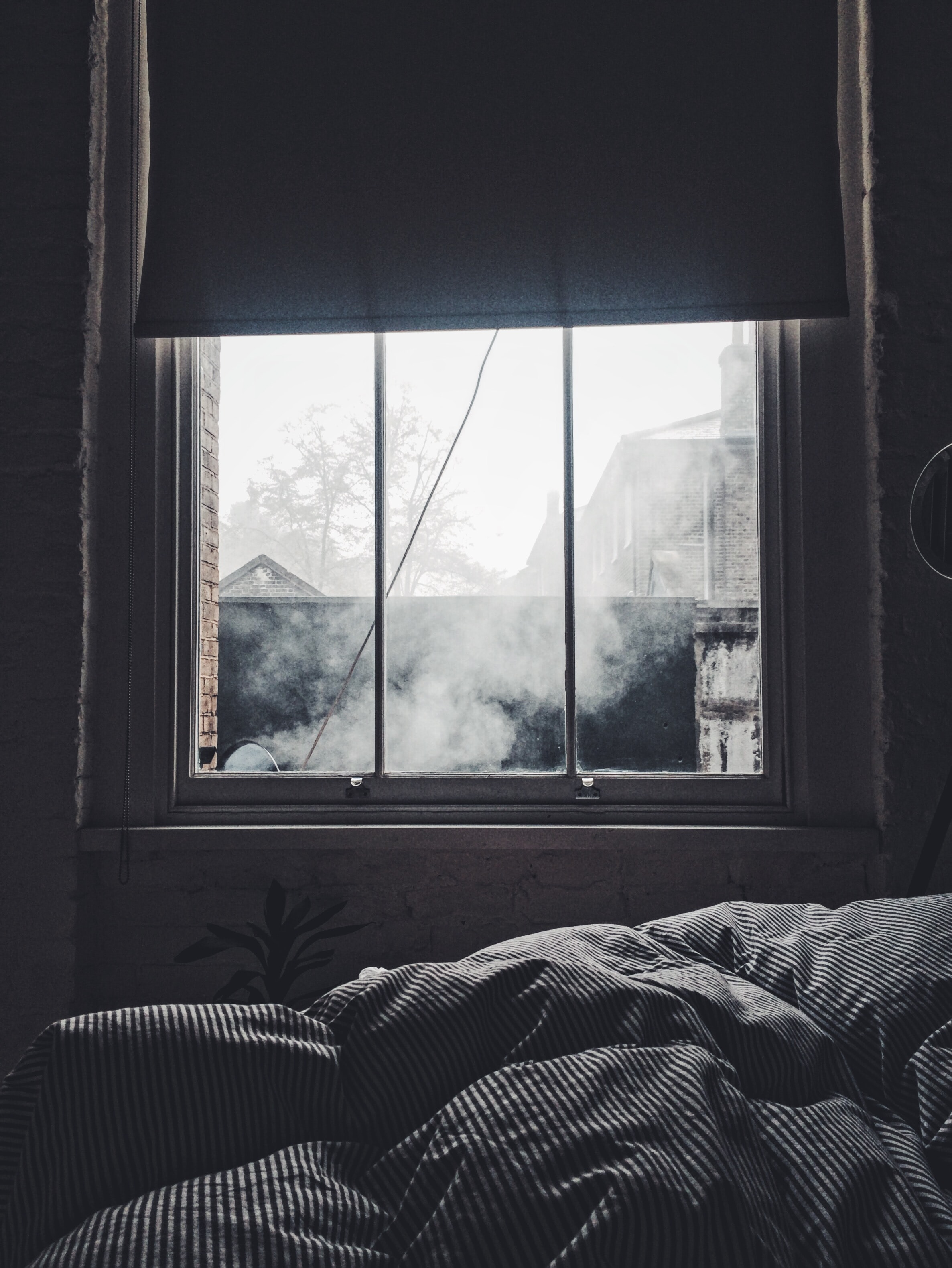 Interior of a bedroom with a blanket and a window showing smoke and other houses outside