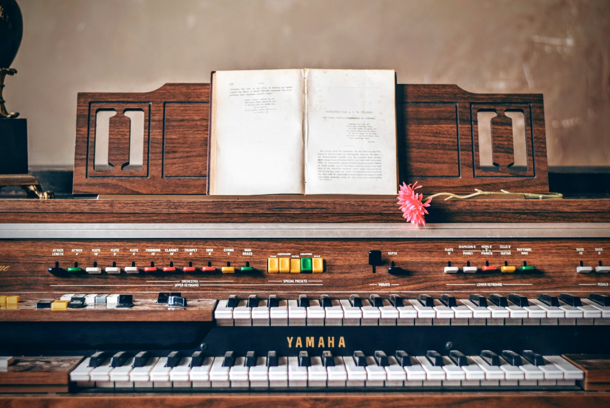 An open book and a pink flower on top of a Yamaha organ