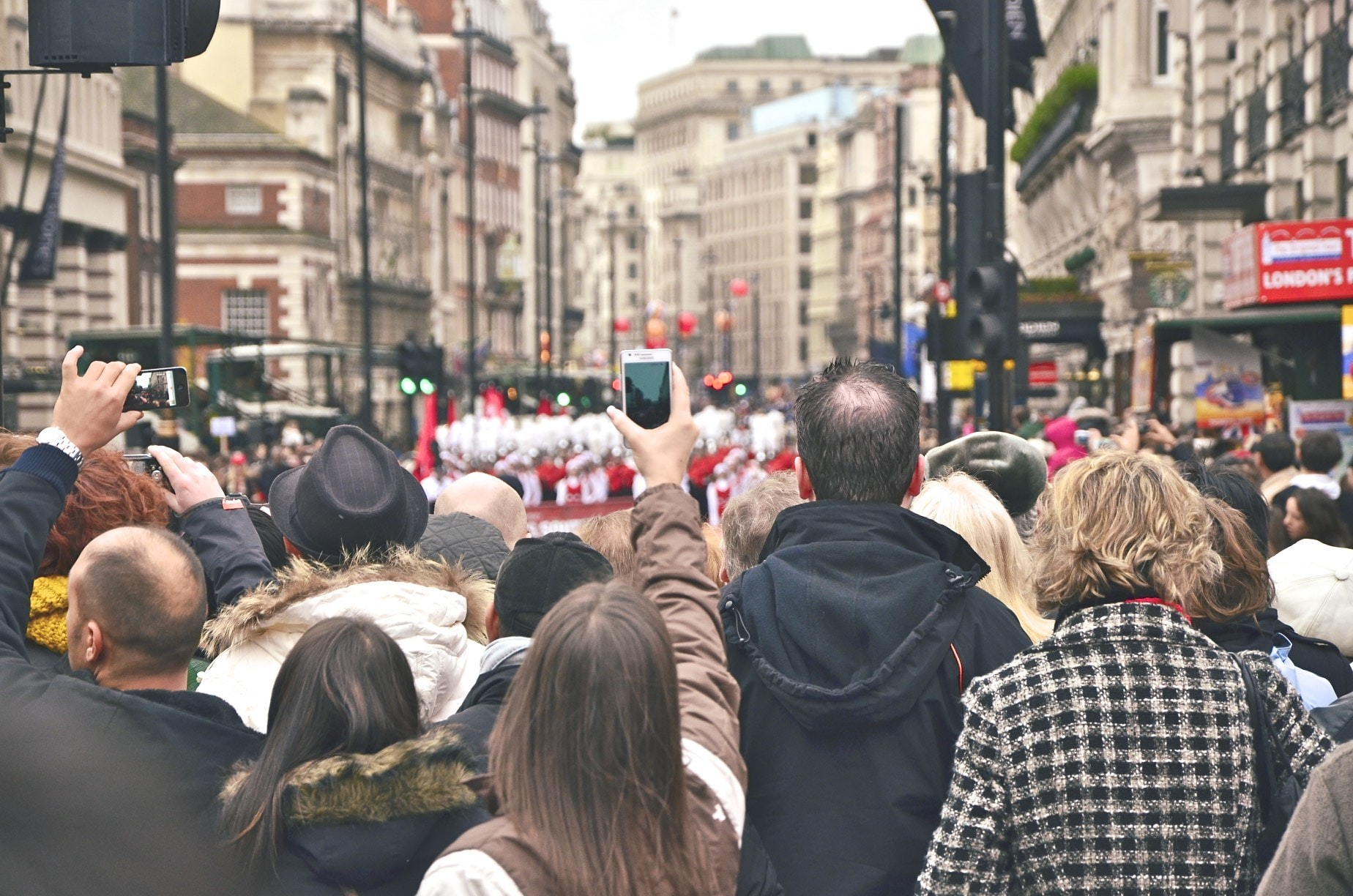 A crowd of people filming a parade in Piccadilly Circus with their smartphones