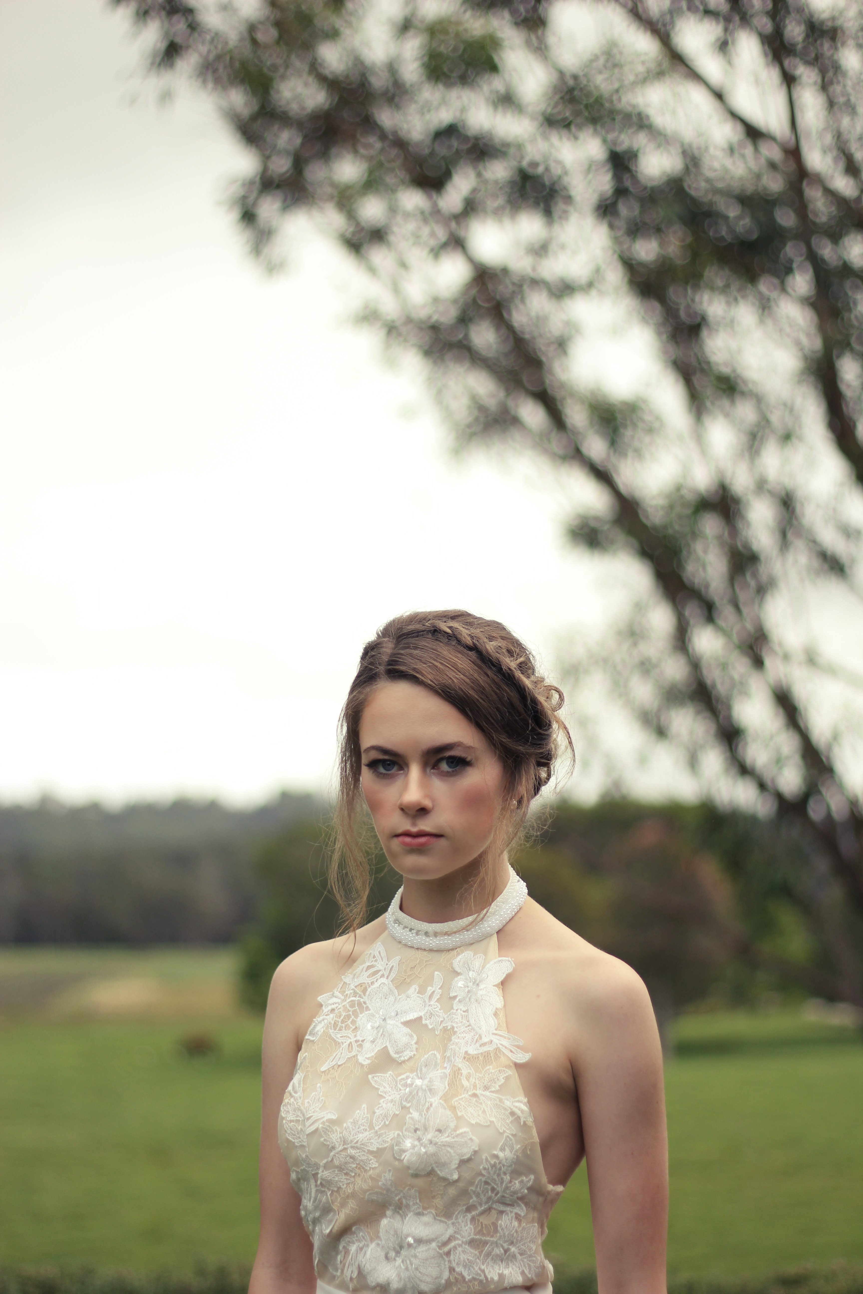 Bride with a braided updo and lace wedding gown outside