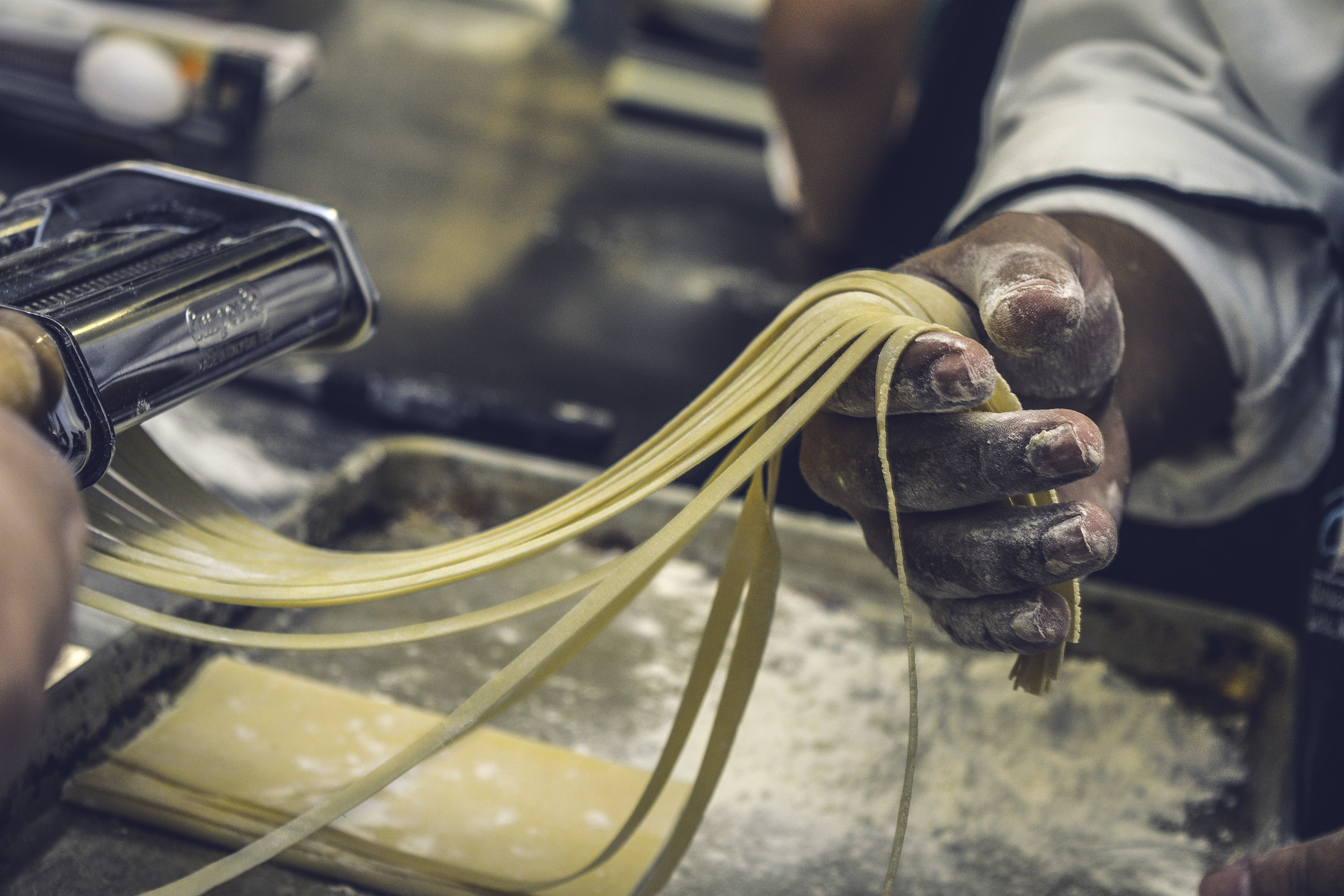 A chef holding long strands of pasta coming out of a machine