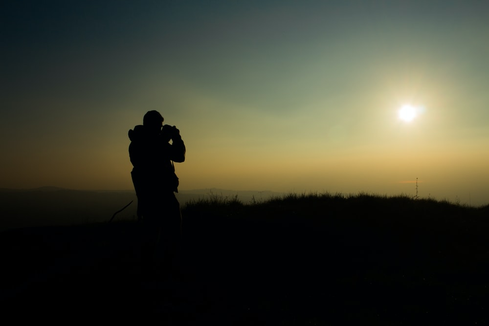 silhouette of man taking picture during golden hour