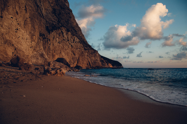 A rocky coastline and waves crashing on a beach in Lefkada