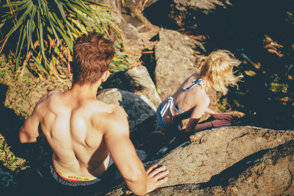 Couple in swimwear climbing down the rocky cliff at Kings Beach
