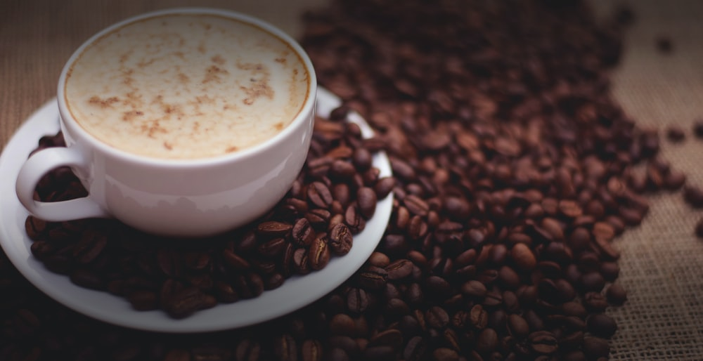 filled white cup on top of white saucer surrounded by coffee beans