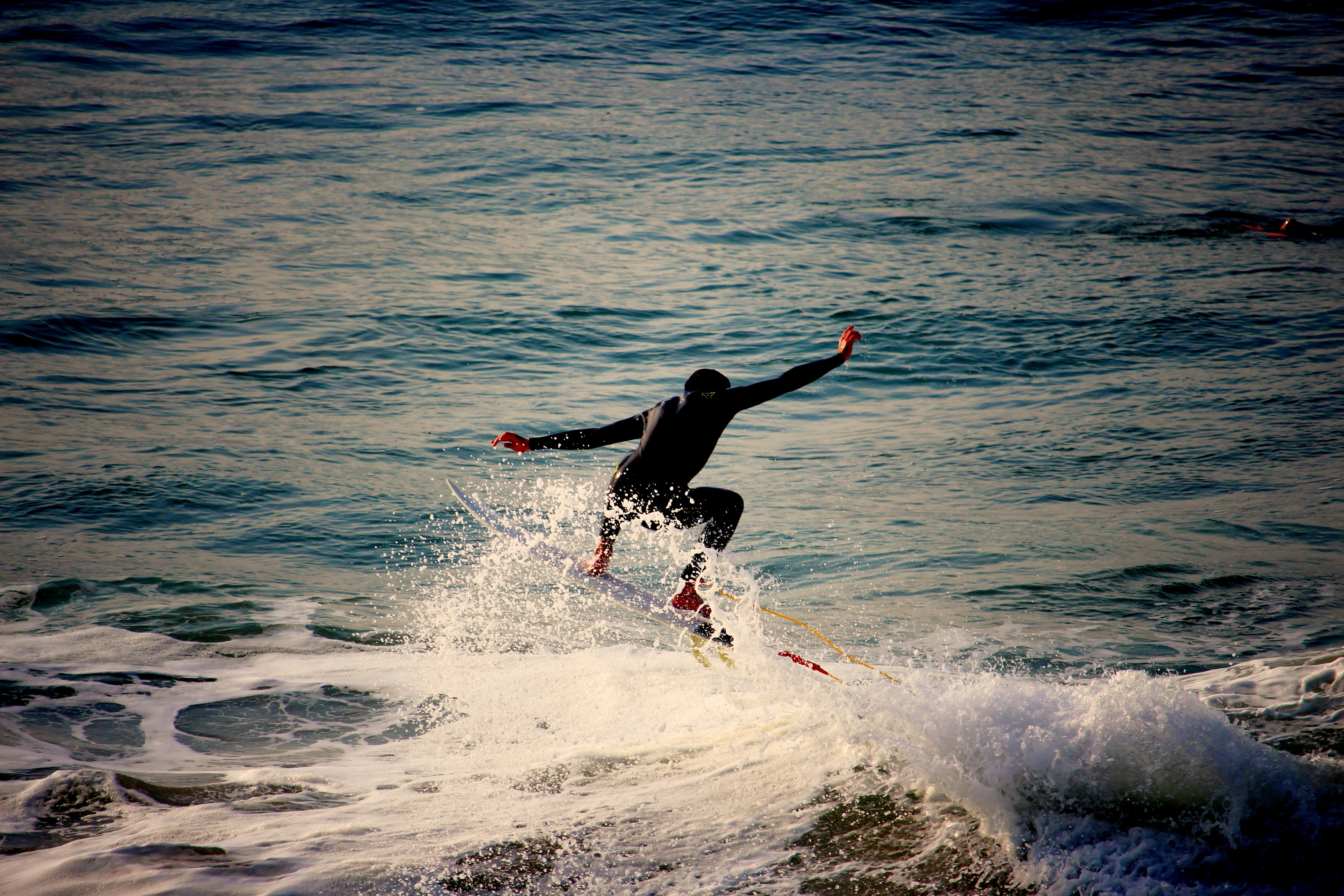 A surfer wearing a wetsuit, arms outstretched in the sea at Biarritz