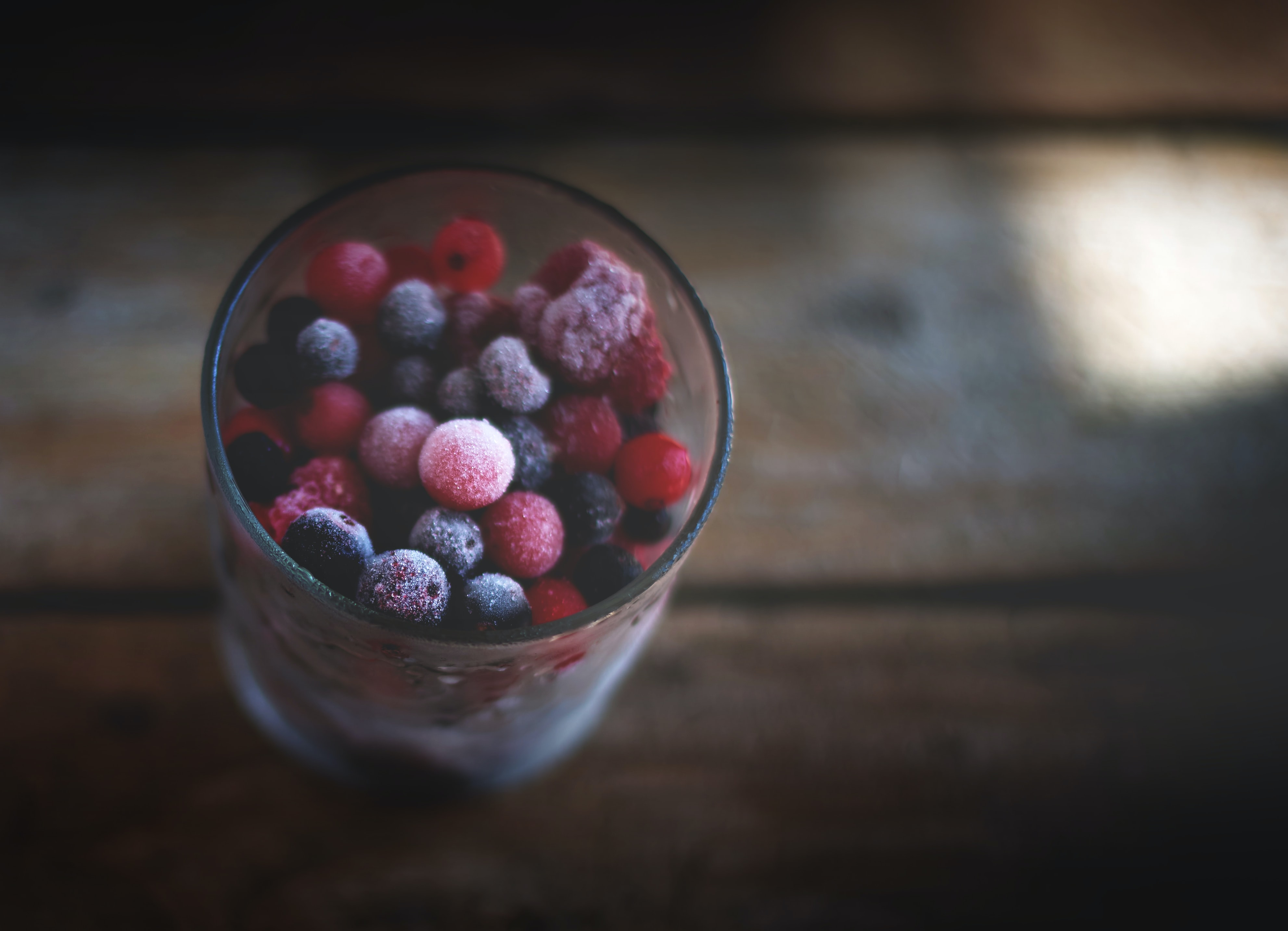 Tall glass of frozen blueberries, raspberries, and assorted berries