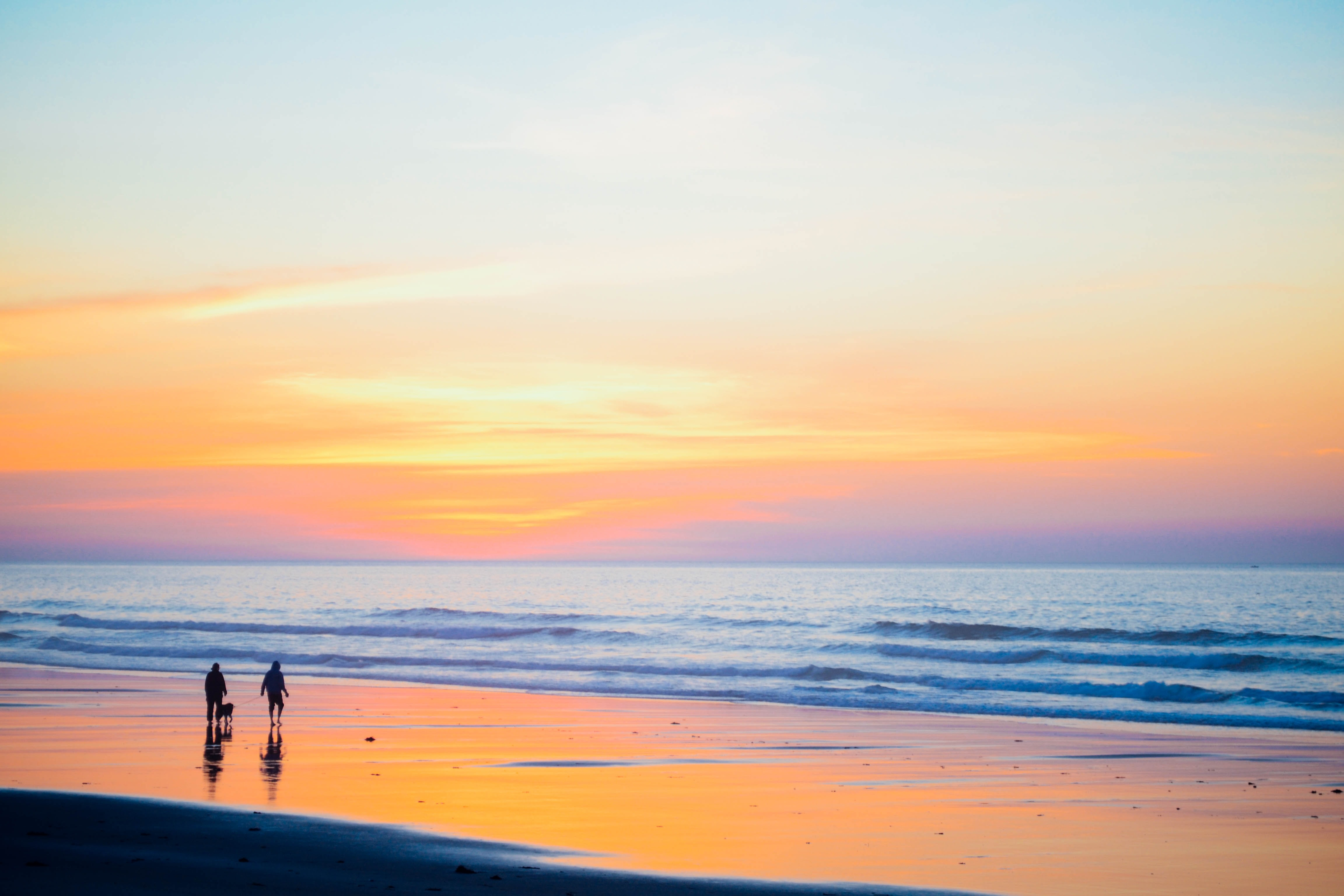 A family by the Moody Beach ocean watching the orange and blue sunset