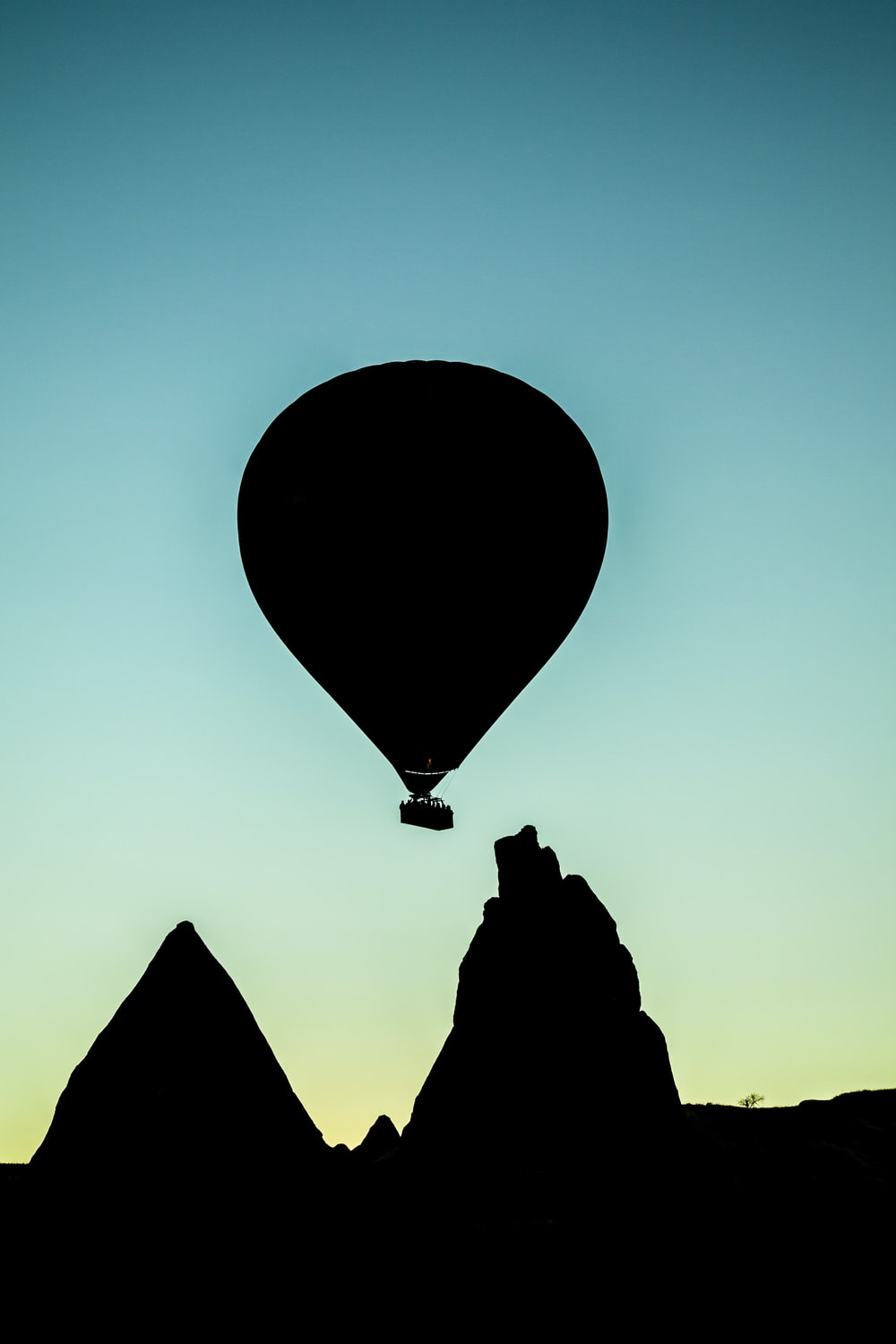 silhouette of hot air balloon flying above rock formation