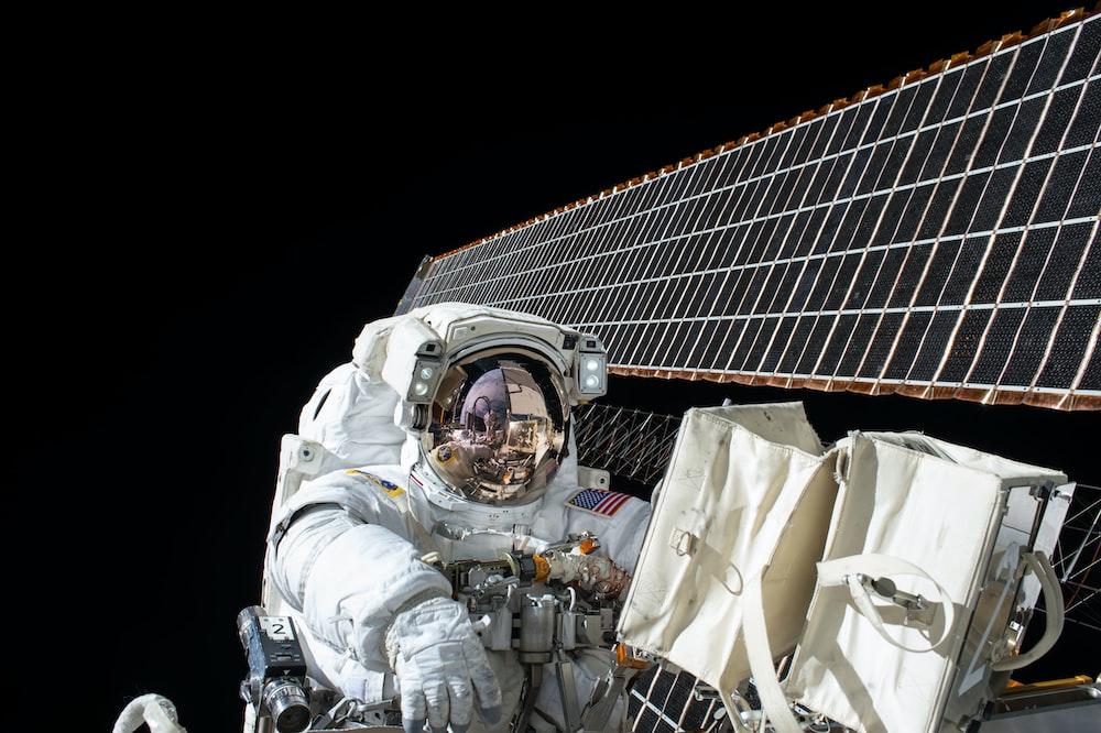 photography of Astronaut beside satellite
