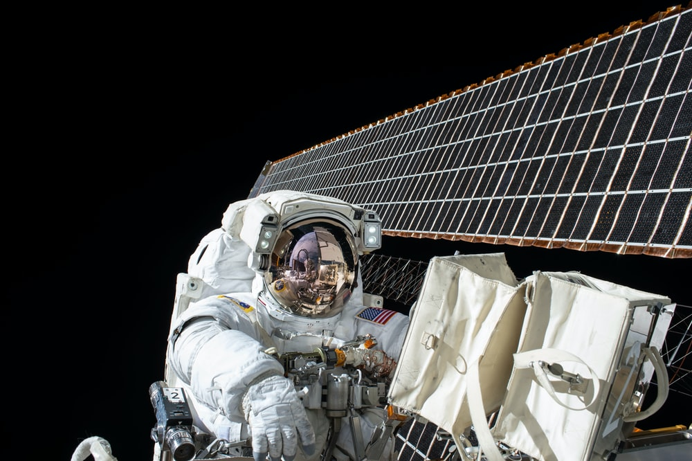 photography of Astronaut beside satellite
