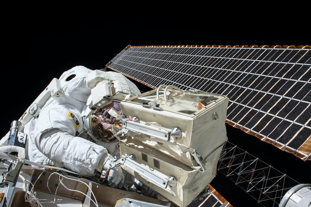 closeup photo of astronaut repairing satellite