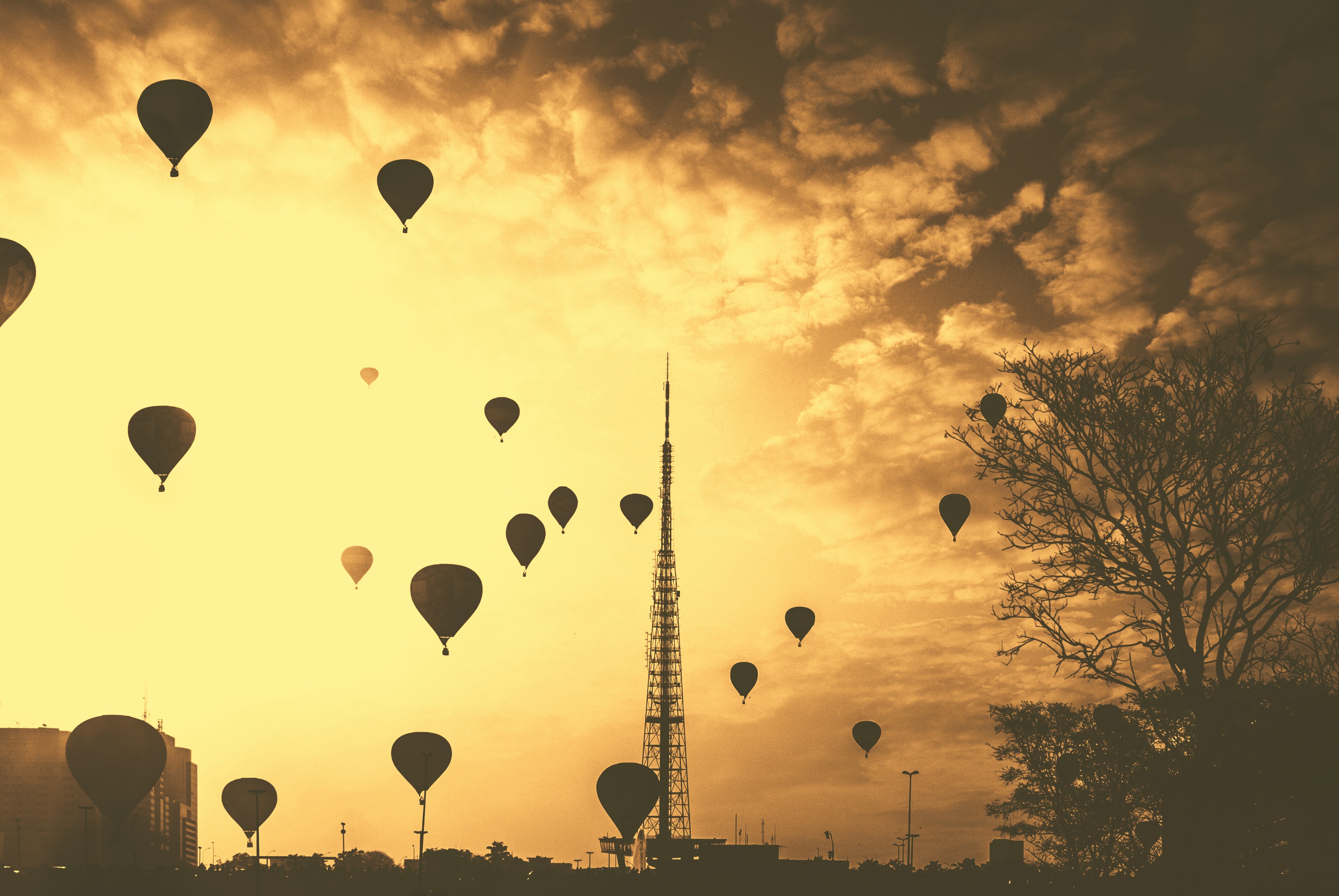 A large number of hot air balloon silhouettes in the orange sky over Brasília