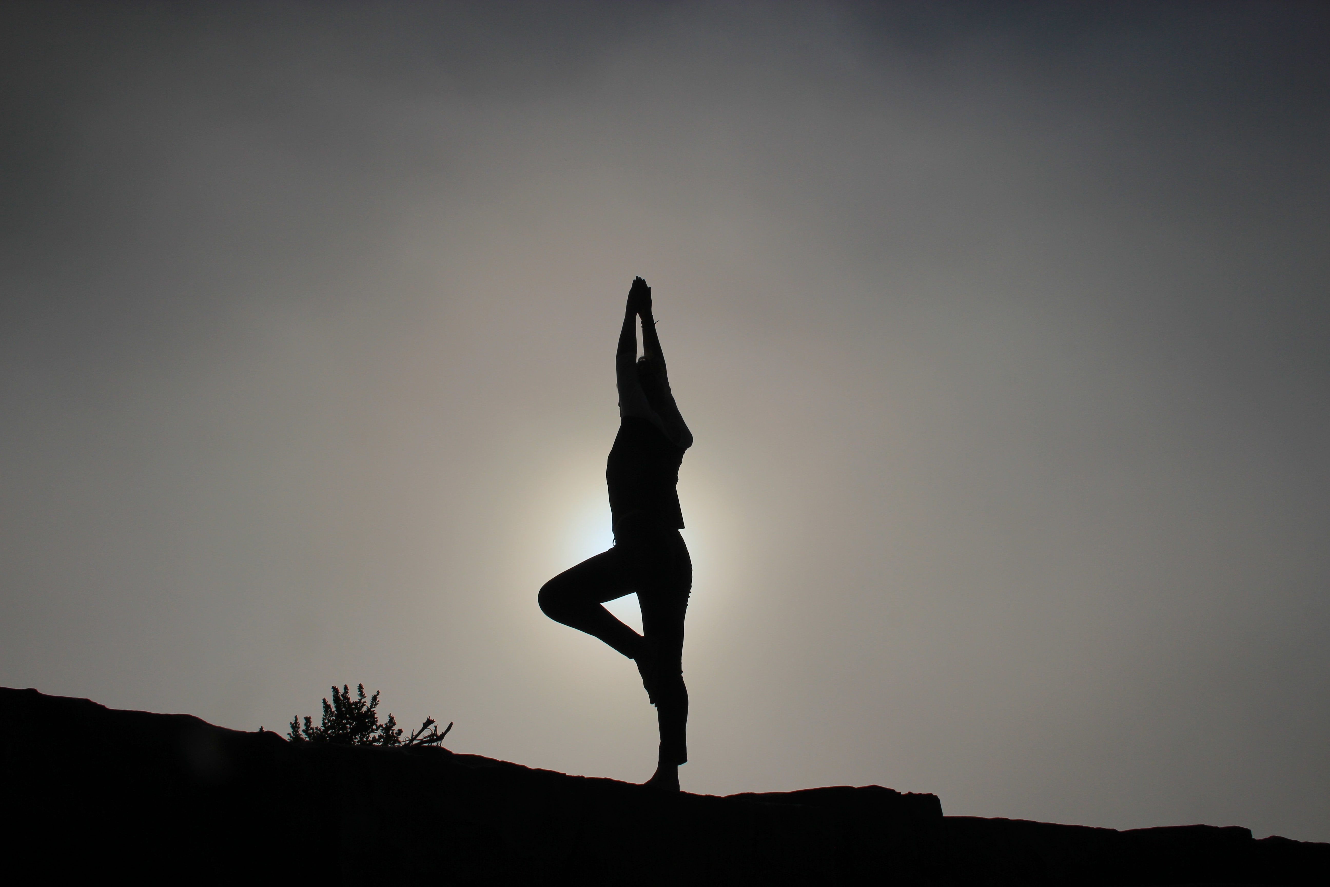 A person doing yoga on a sloping ground in silhouette