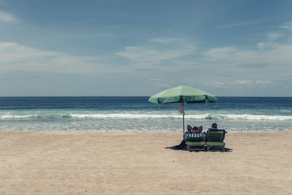 people sitting on seashore under green umbrella during daytime