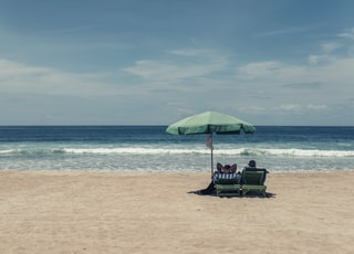 people sitting on seashore under green umbrella during daytime