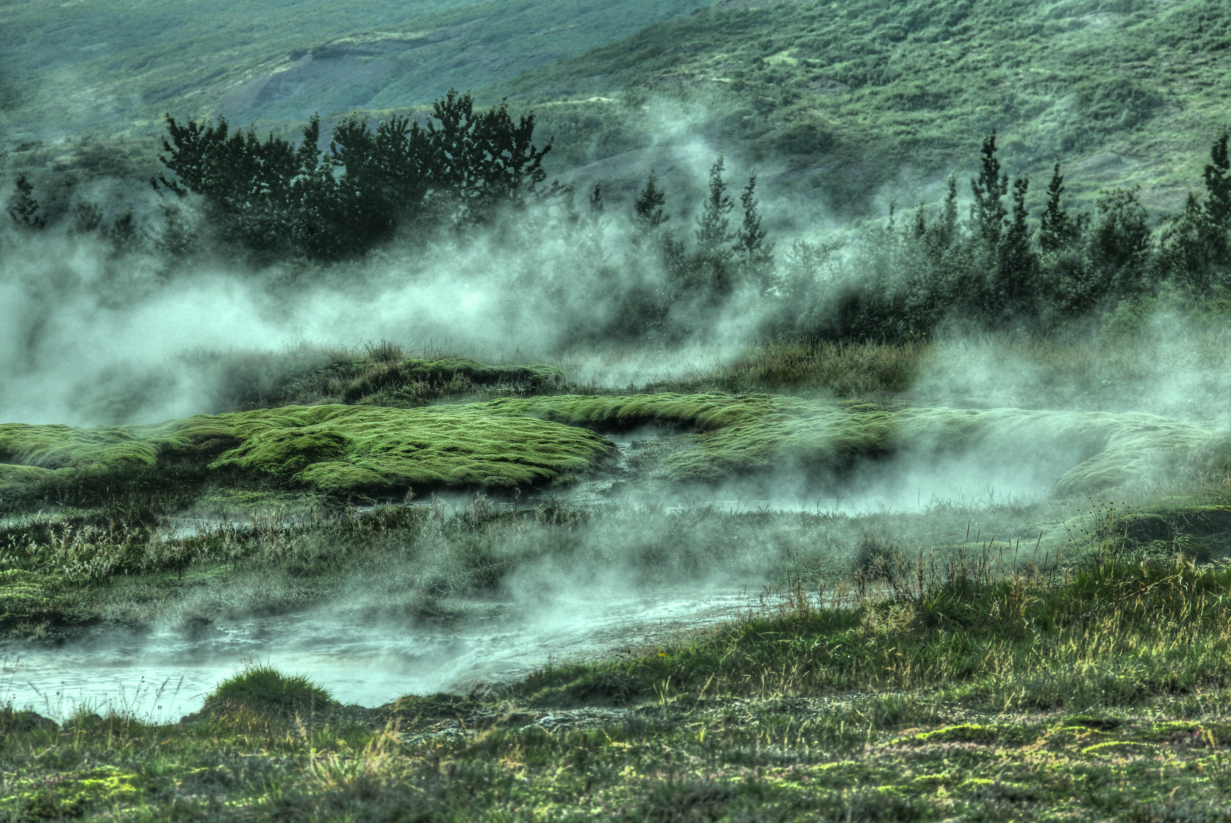 Steam rising above the mossy rocks near Strokkur Geyser