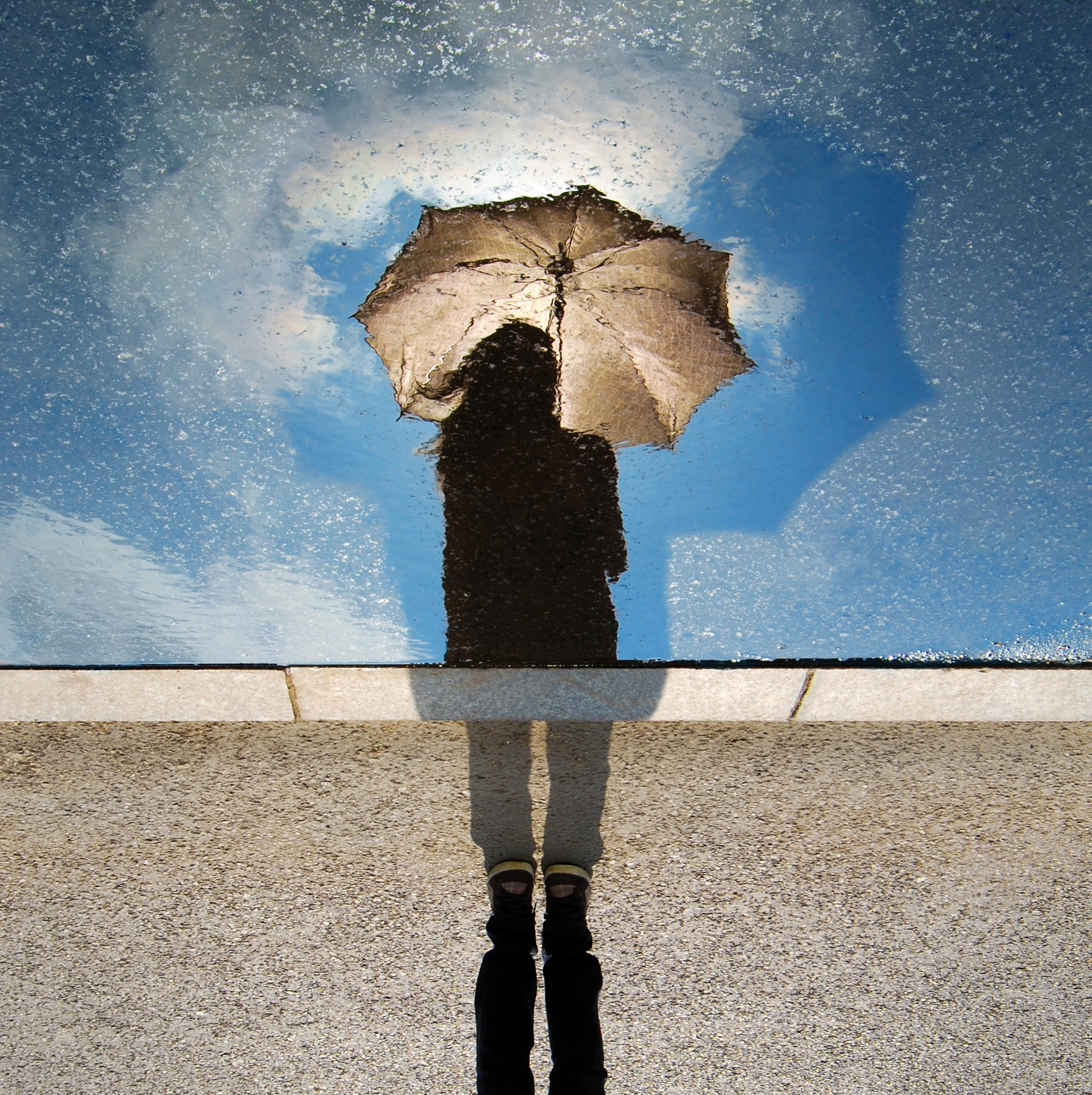 person standing on gray surface while holding umbrella