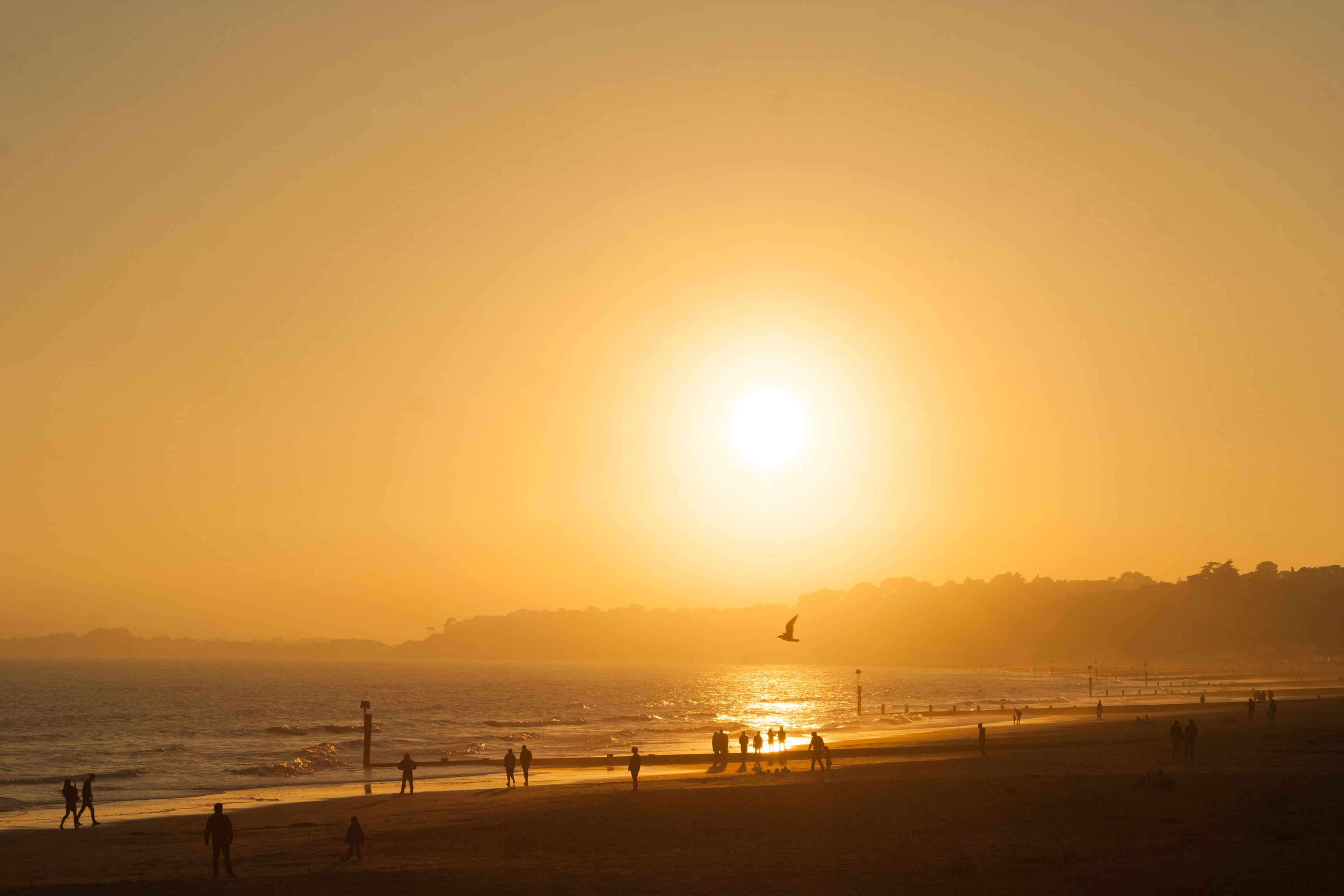 The horizon features the sunset casting yellow color over beach in Bournemouth
