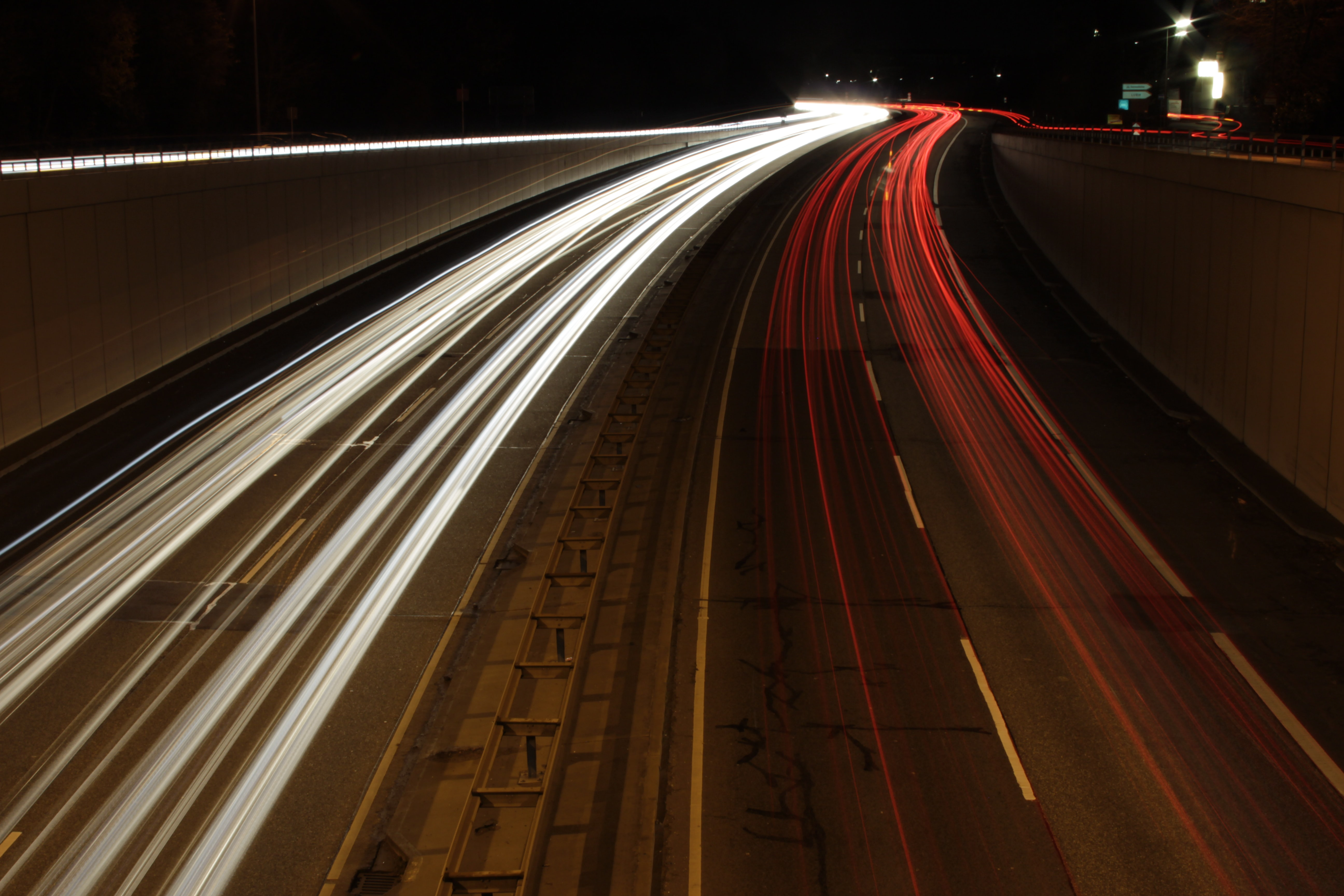 White and red light trails on a two-lane highway at night