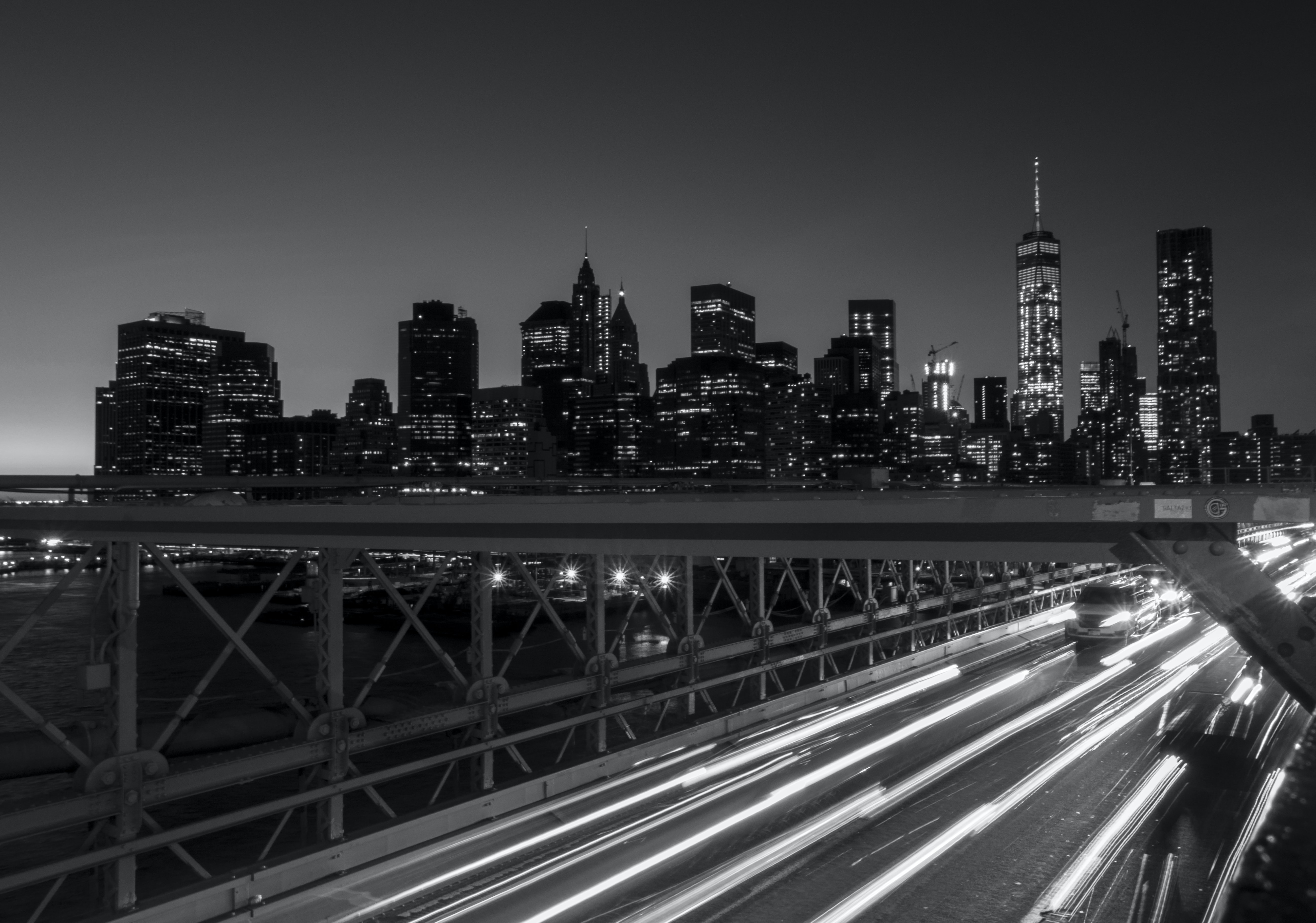 Black and white long exposure view at night over the Brooklyn Bridge