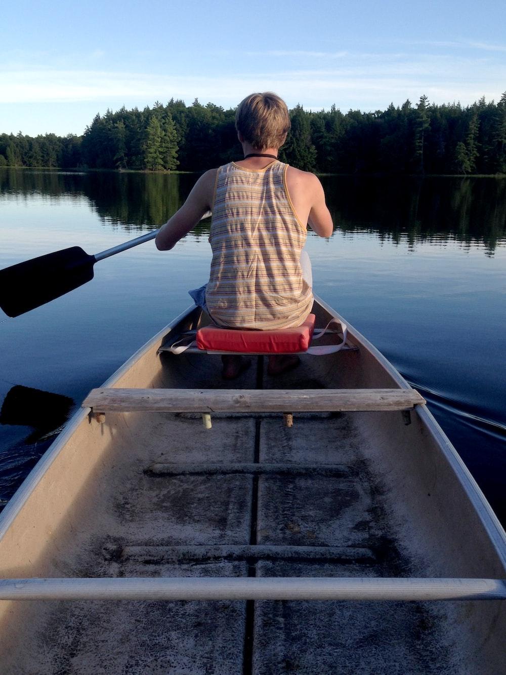 man sitting on boat at daytime