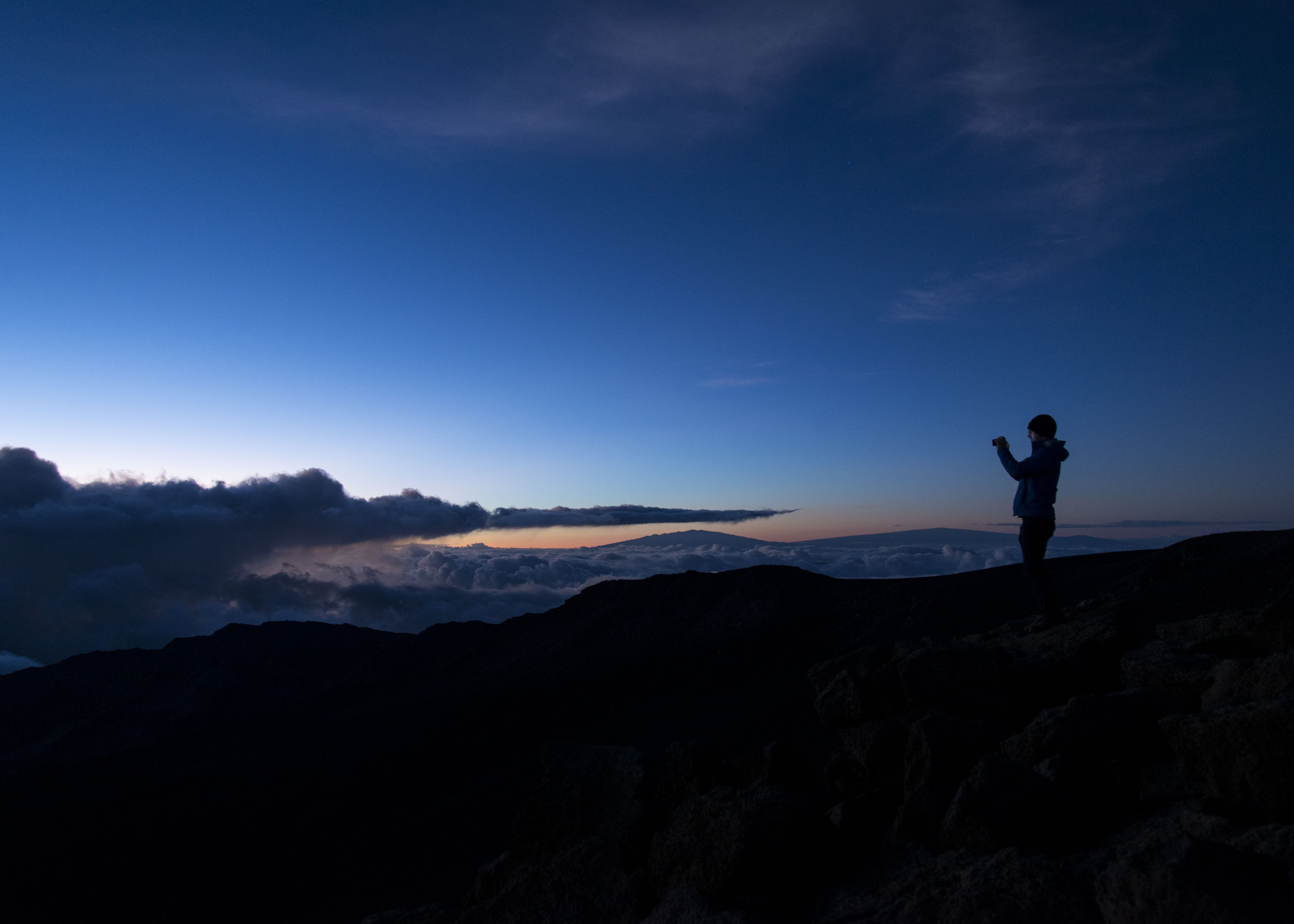 silhouette of man taking photo on rock cliff