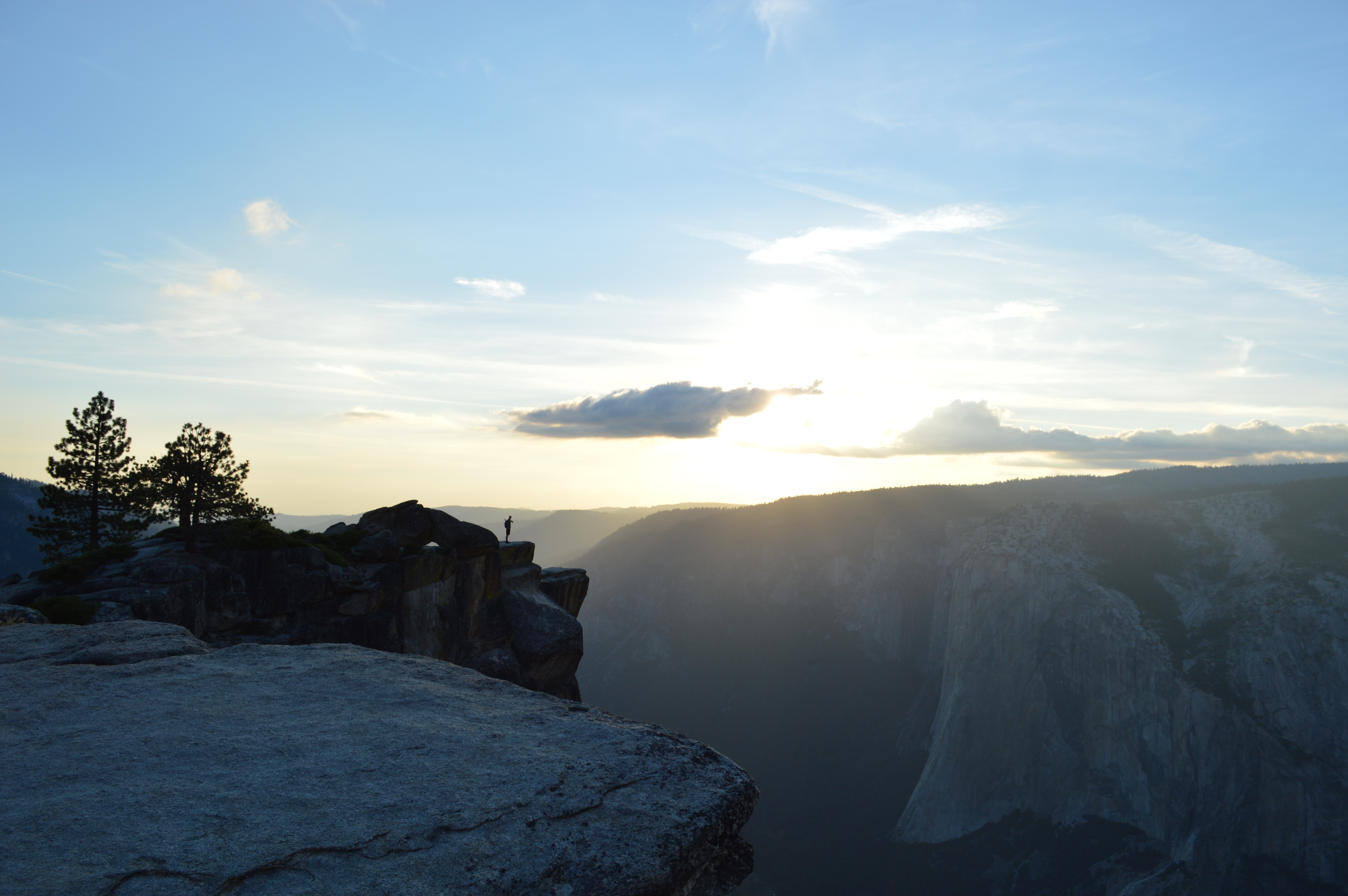 A distant shot of a silhouette of a person standing on a rocky ledge over Yosemite Valley