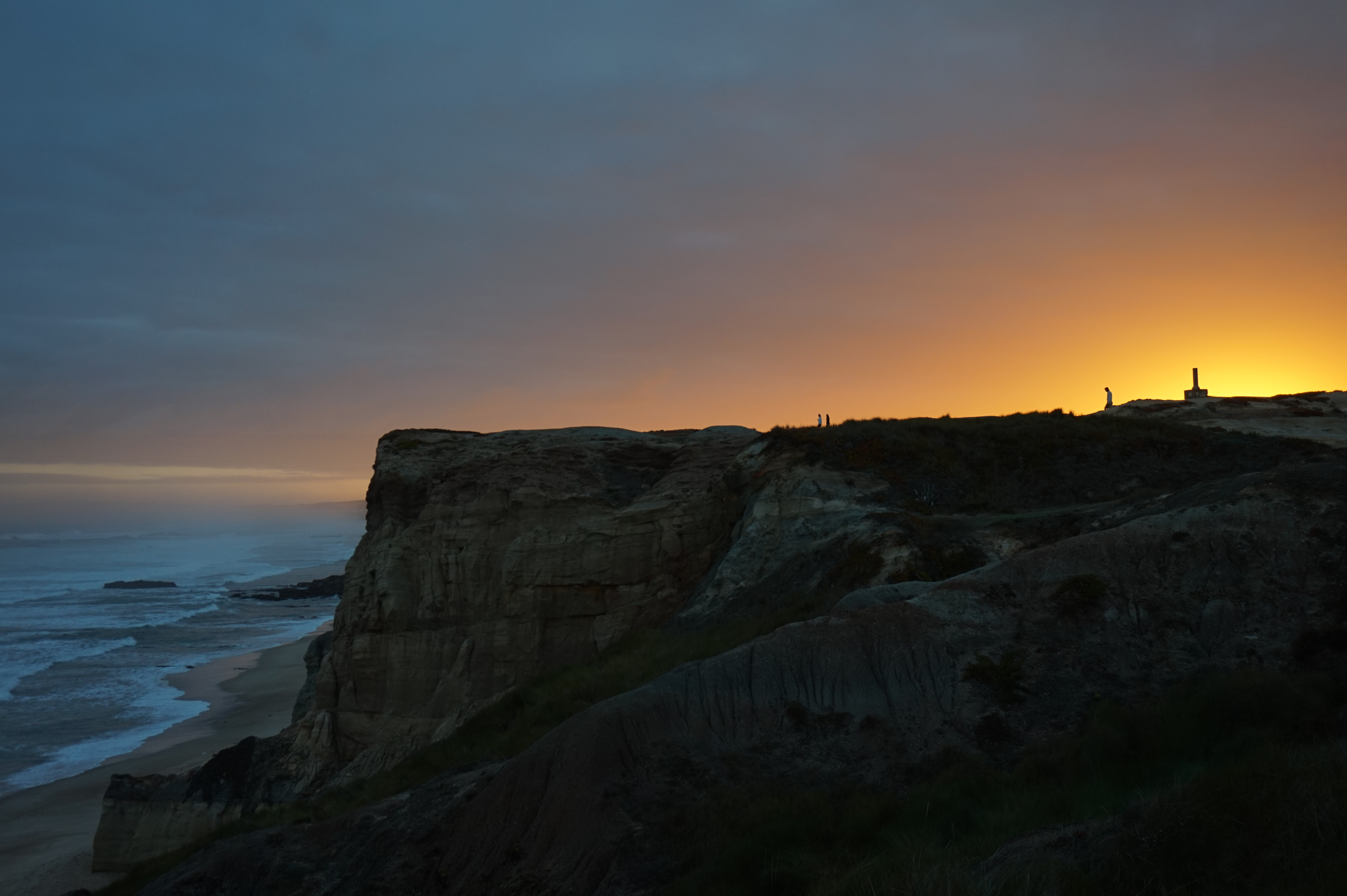 Landscape shot featuring beach and ocean at the foot of  humongous cliff in Peniche