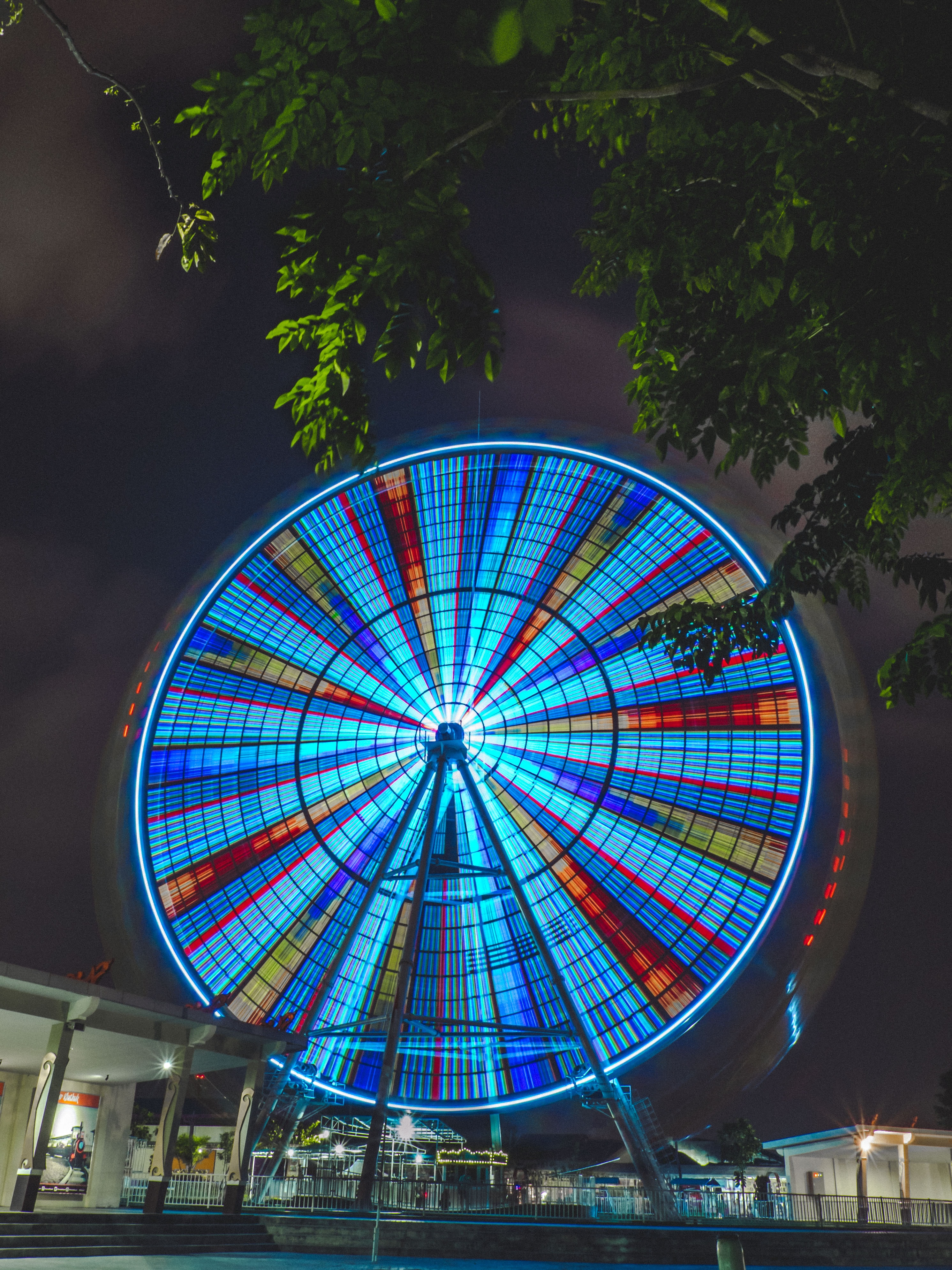 A bright and colorful ferris wheel spinning in circles in the middle of the night