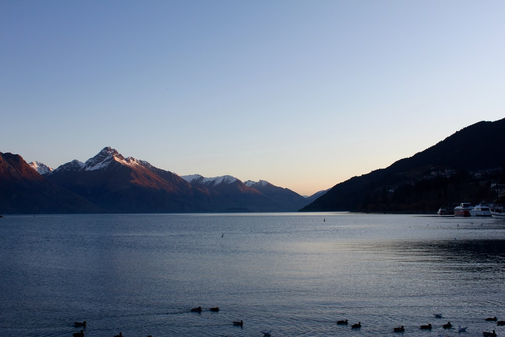 photography of calm body of water near mountains at daytime