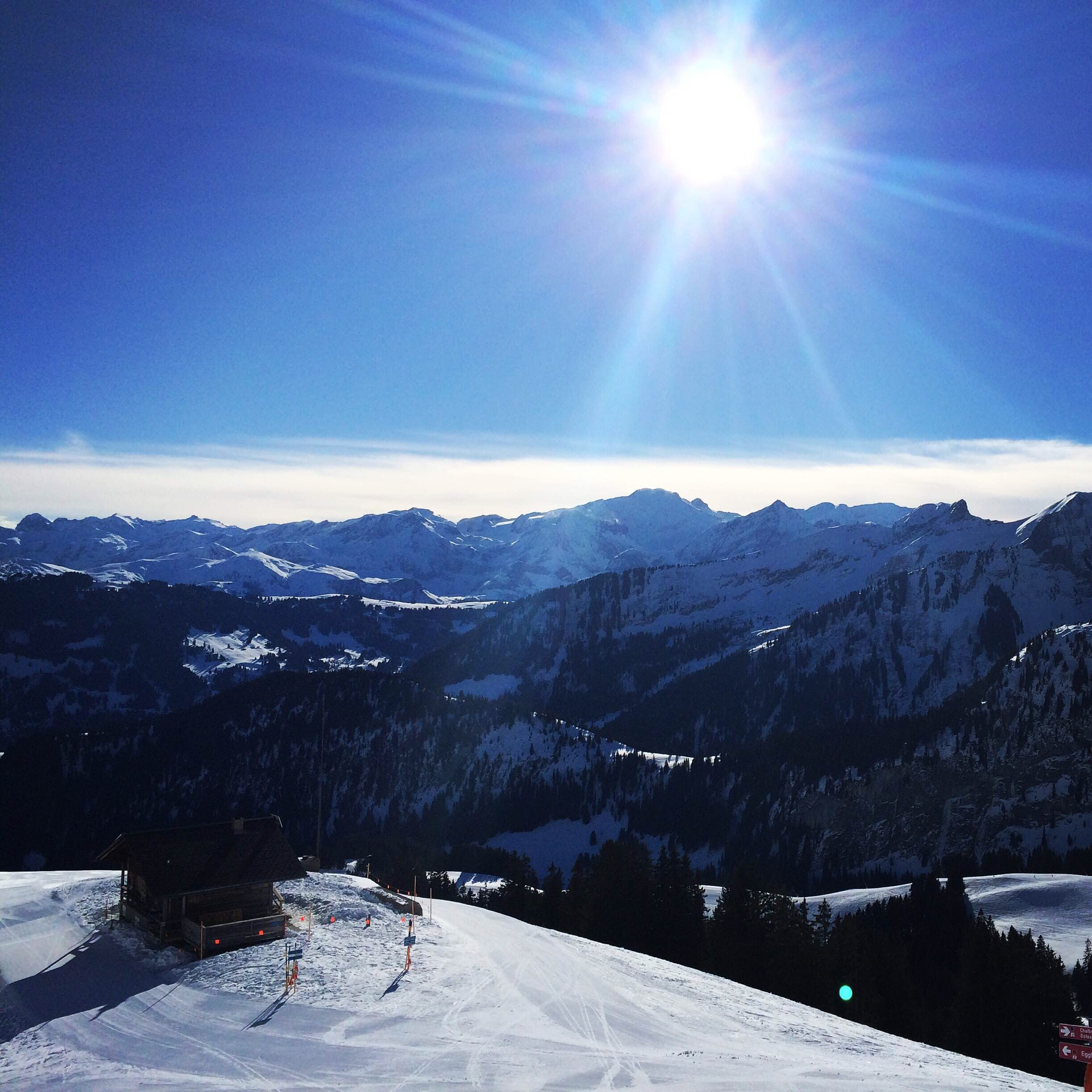 A view on a snowy mountain resort with the sun high in the sky