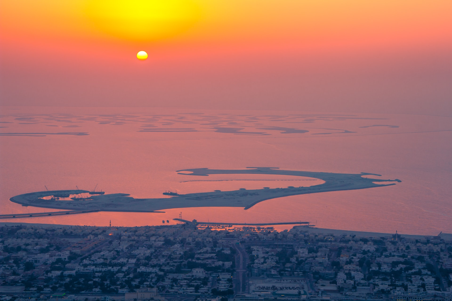 An abstract-shaped artificial island on a body of water during sunrise