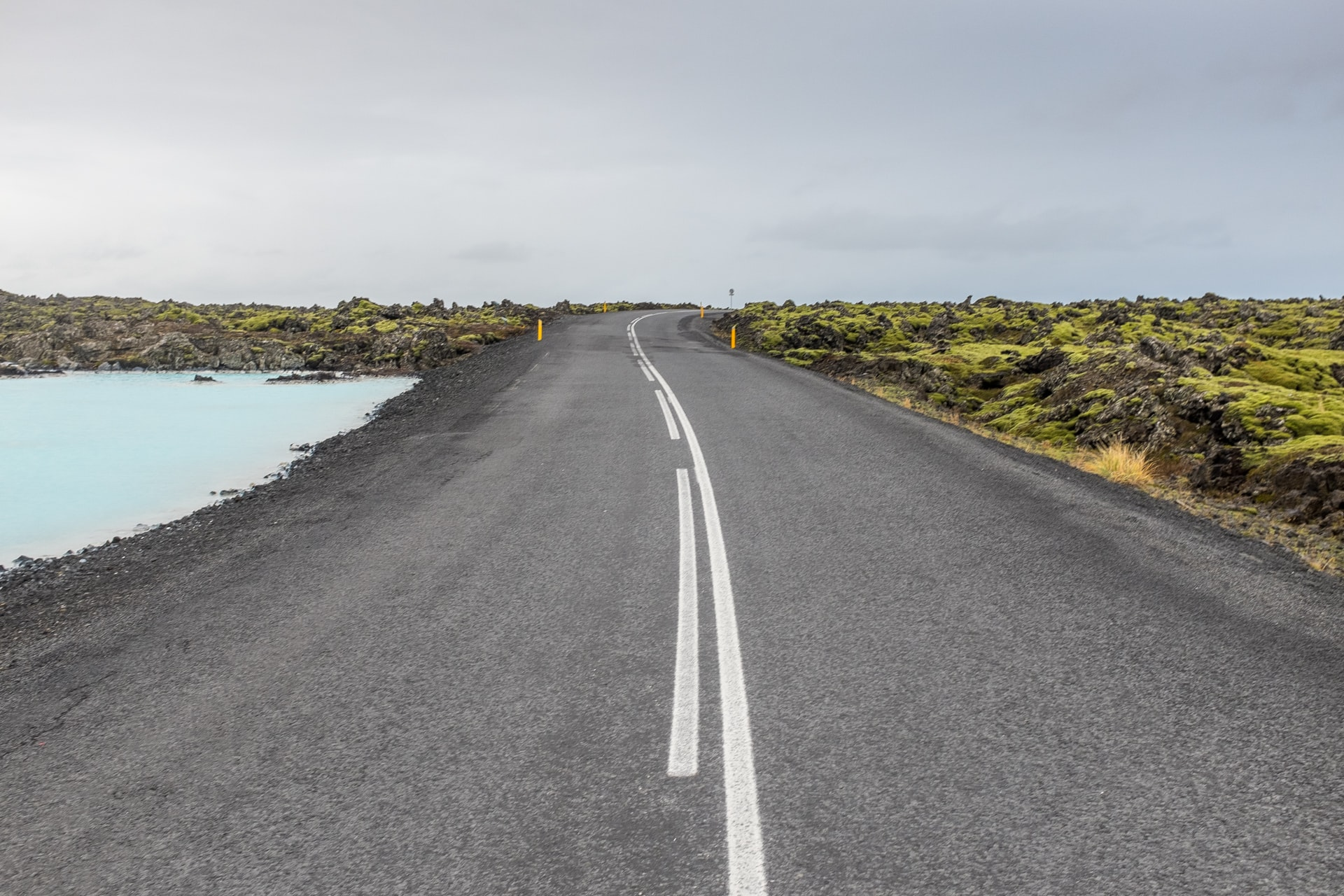 A concrete road between light blue water and flat mossy rocks under a dull sky