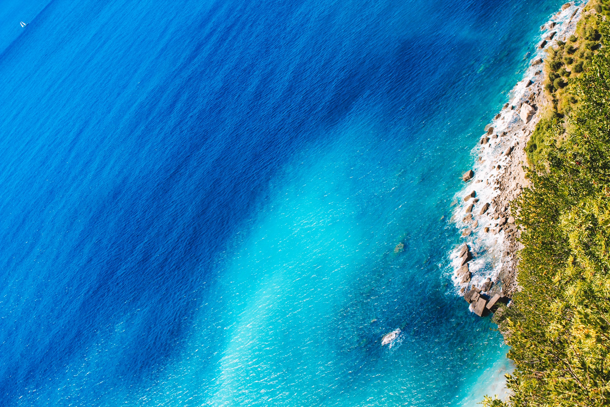 A drone shot of the deep blue sea and a rocky beach in Cinque Terre