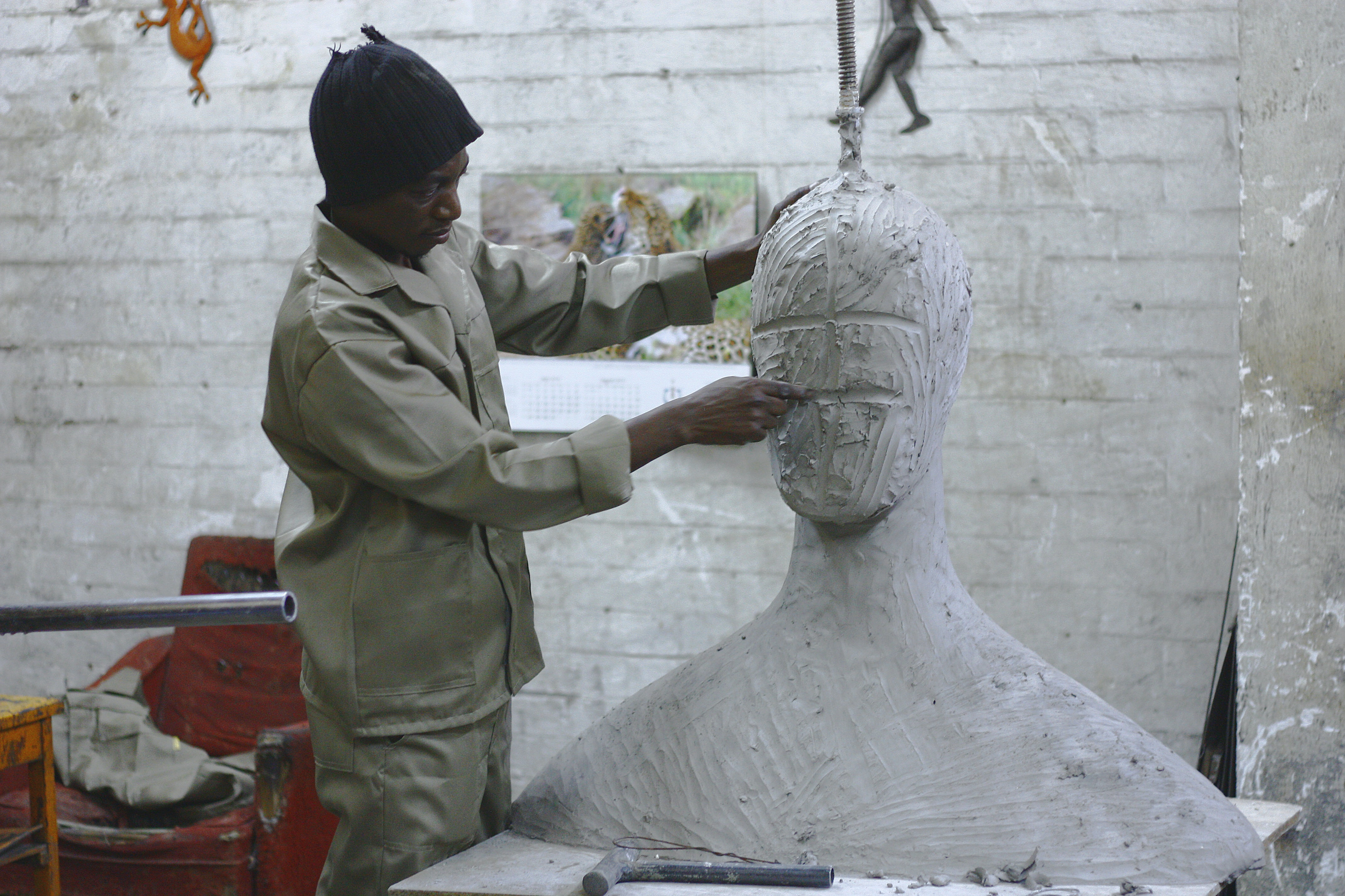 A sculptor works in his studio sculpting a large white body and head