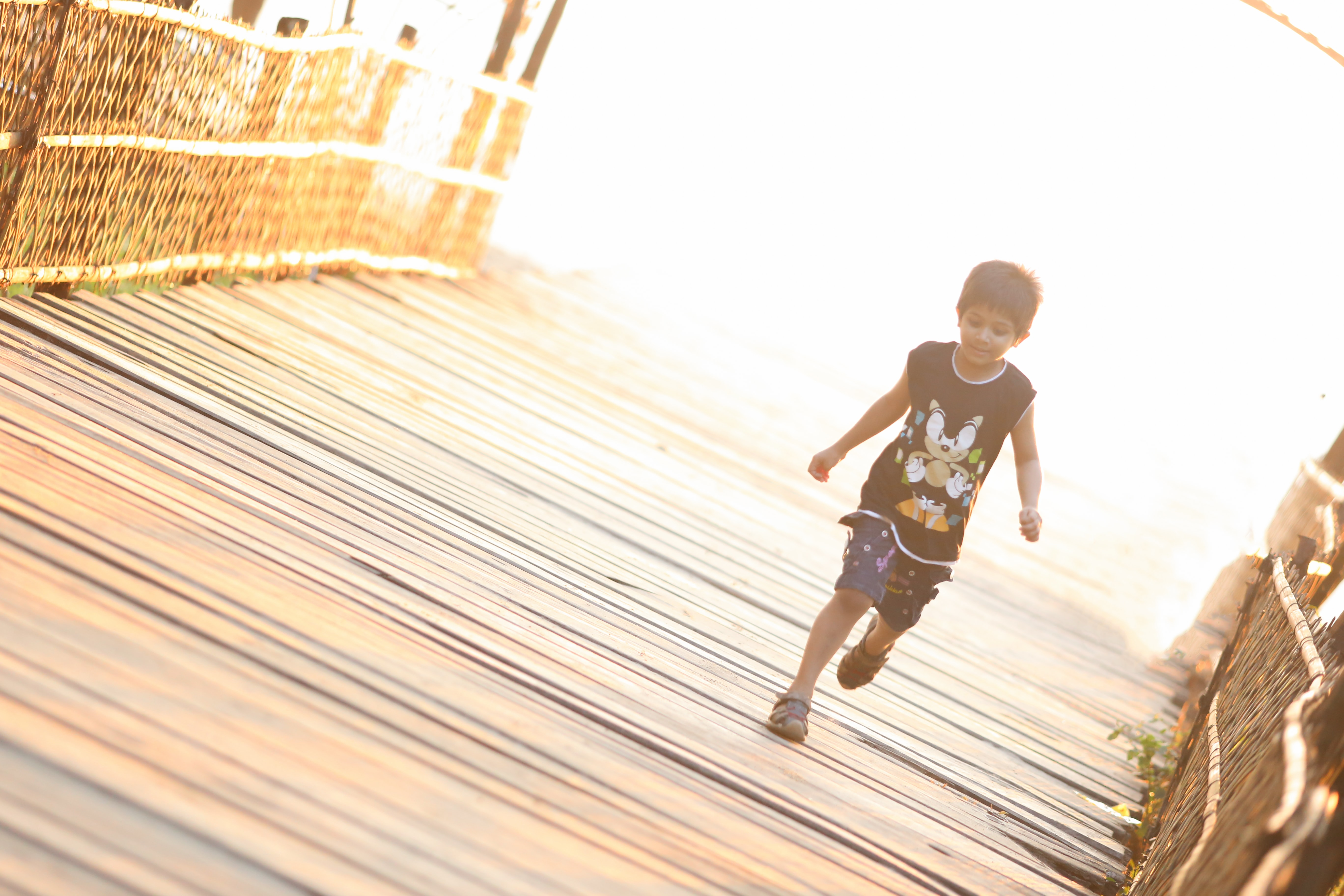 Male child wearing a Sonic t-shirt and sandals running across a wooden bridge in Bangladesh