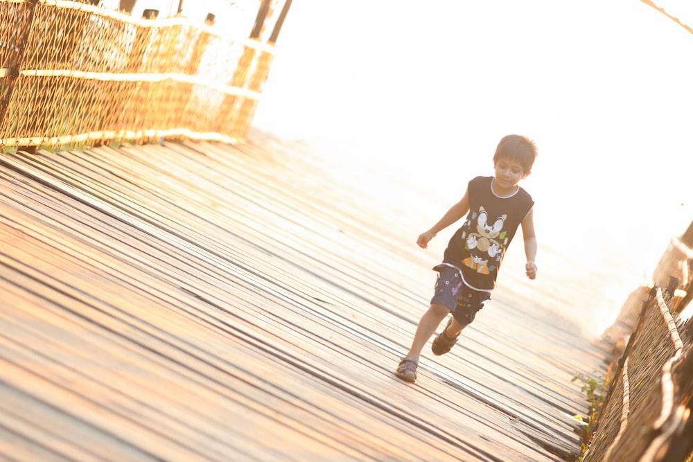 boy walking on brown wooden bridge