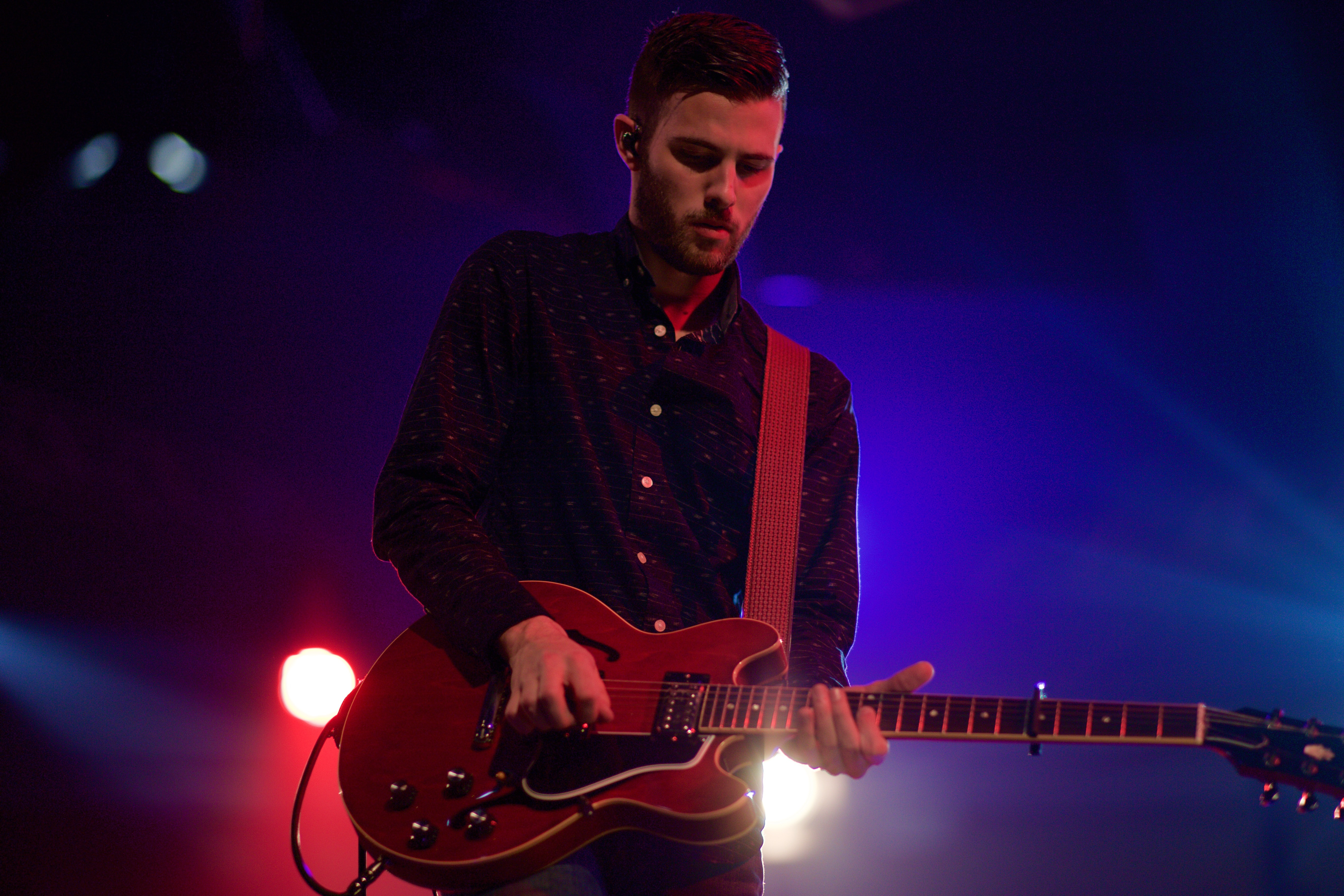 A male guitarist in a shirt performing on stage with blue and red lights behind him