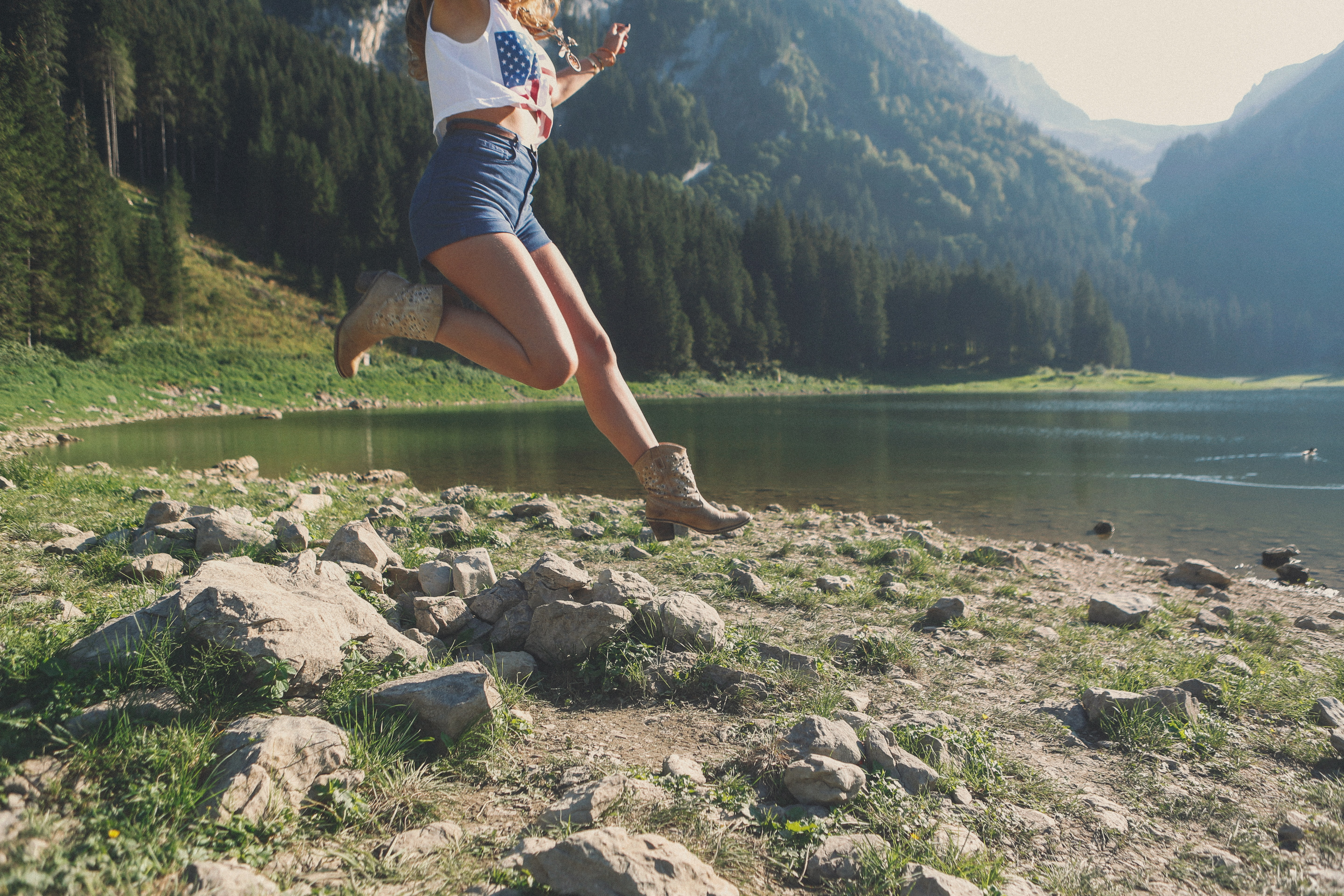 A woman in cowboy boots jumping over rocks on a shore of a mountain lake
