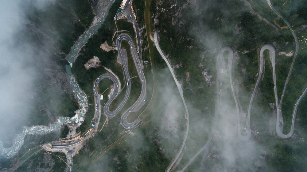 bird's eye view photography of curved pave road
