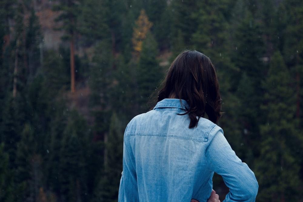 woman facing pine trees