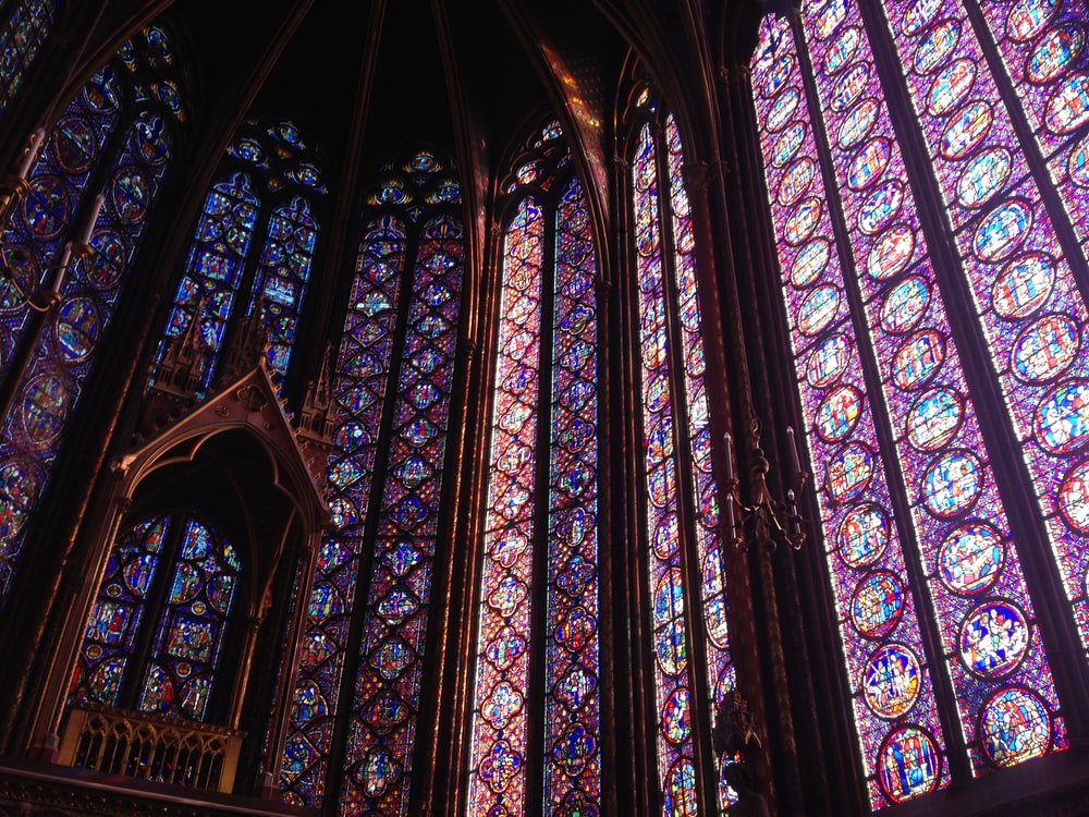 Colorful religious stained glass windows inside of a church cathedral.