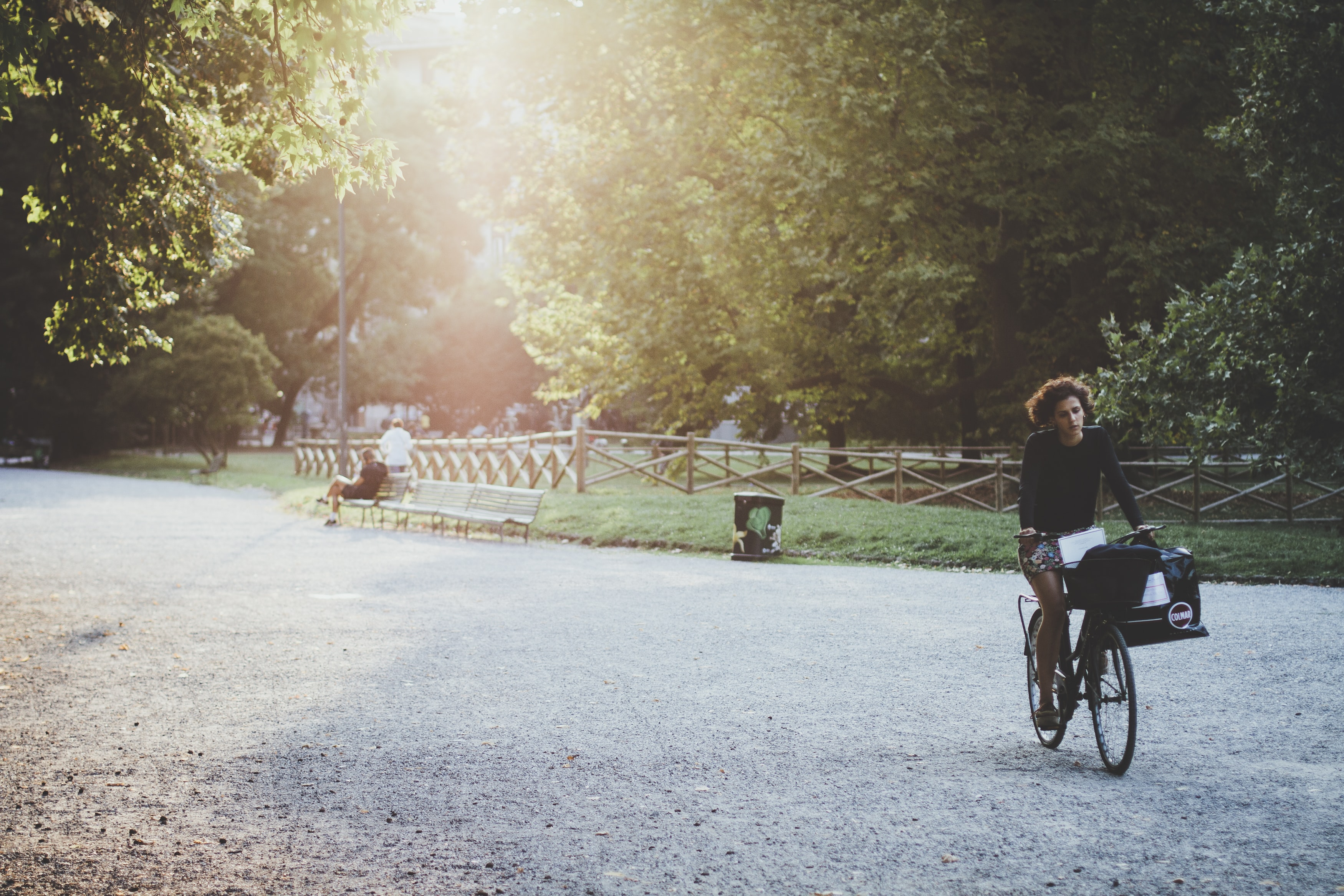 A woman riding a bicycle in a park lane on a sunny evening