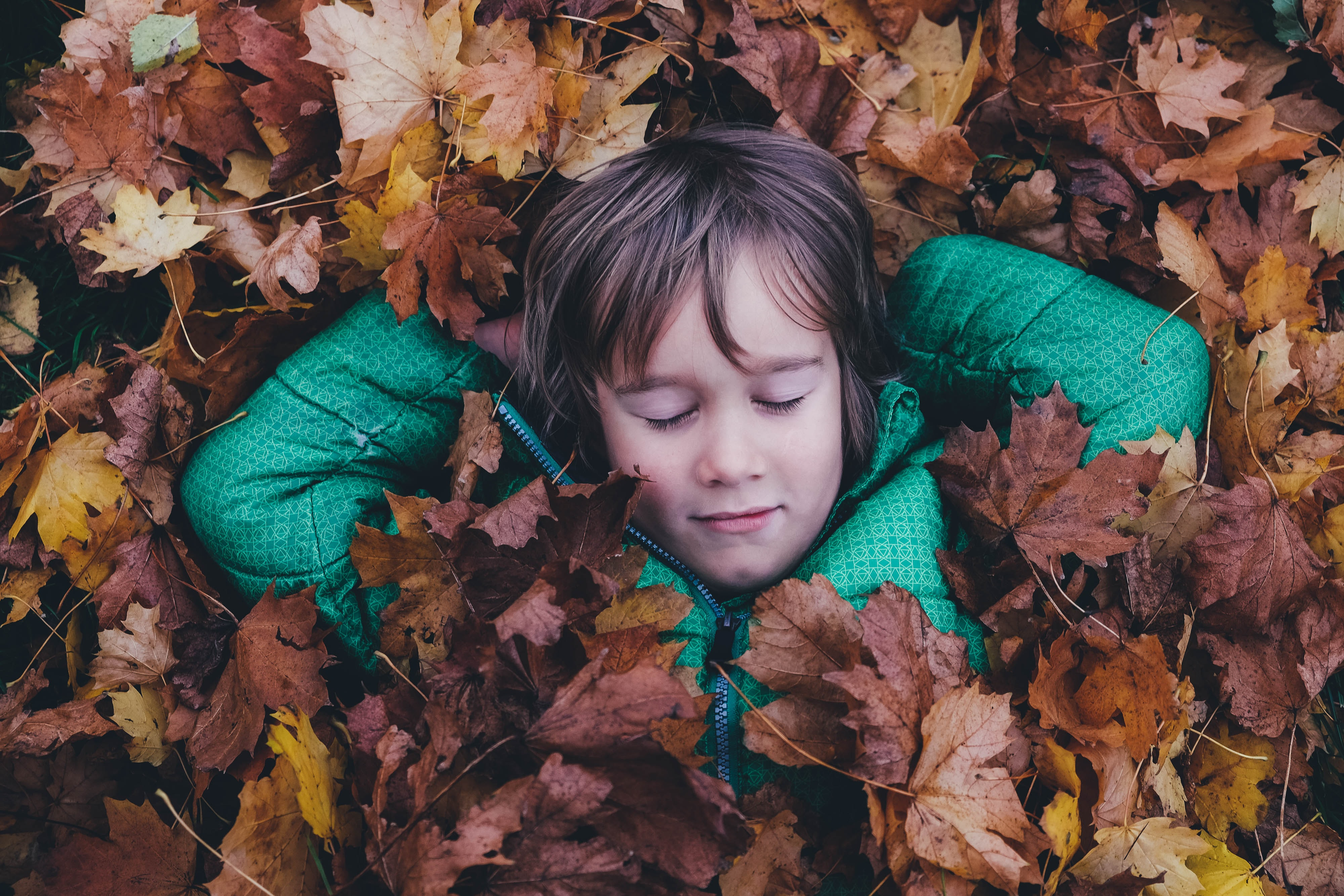 A child lying on the ground under a thick layer of autumn leaves