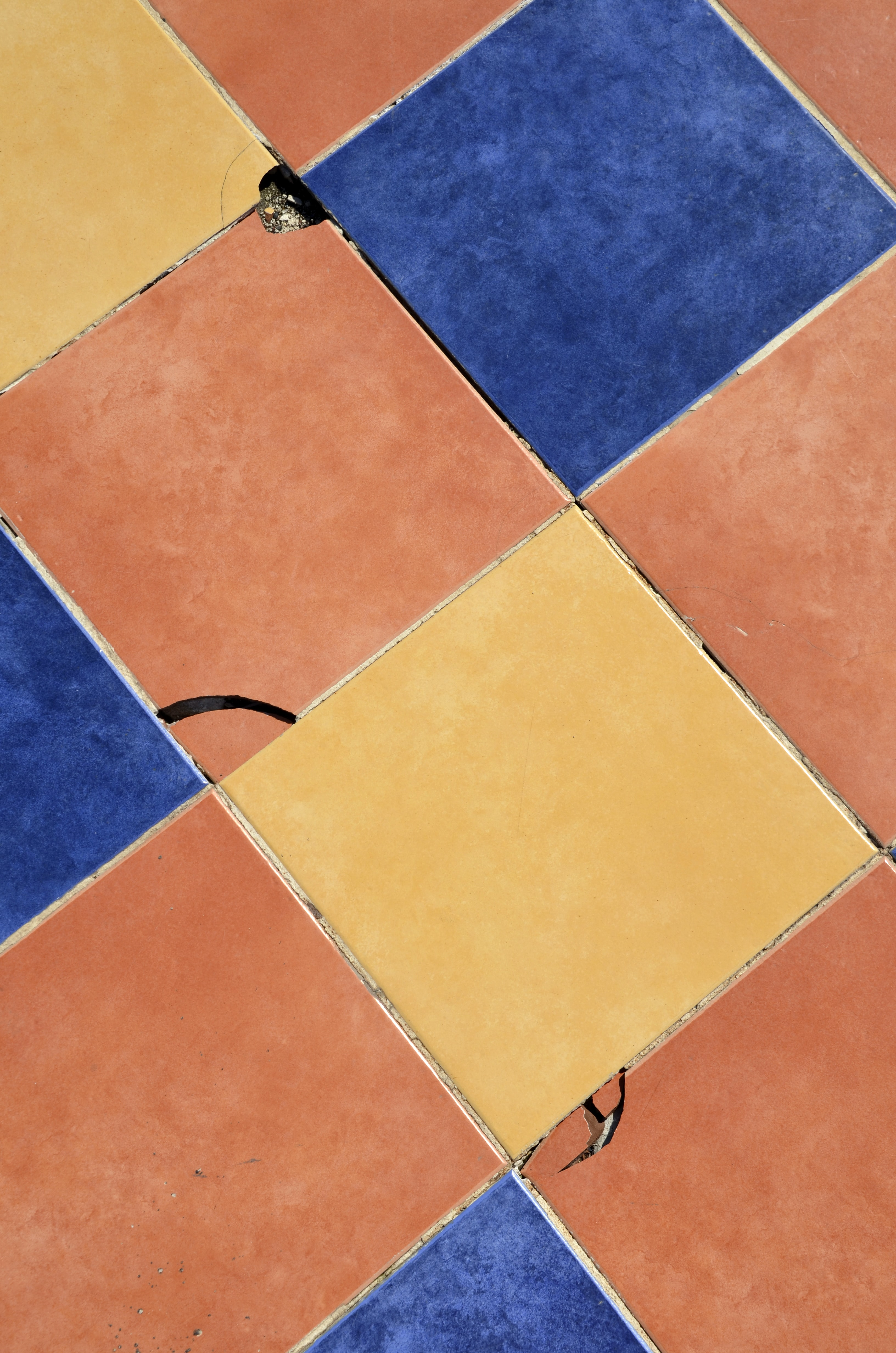 close-up photography of blue, orange, and yellow tile surface