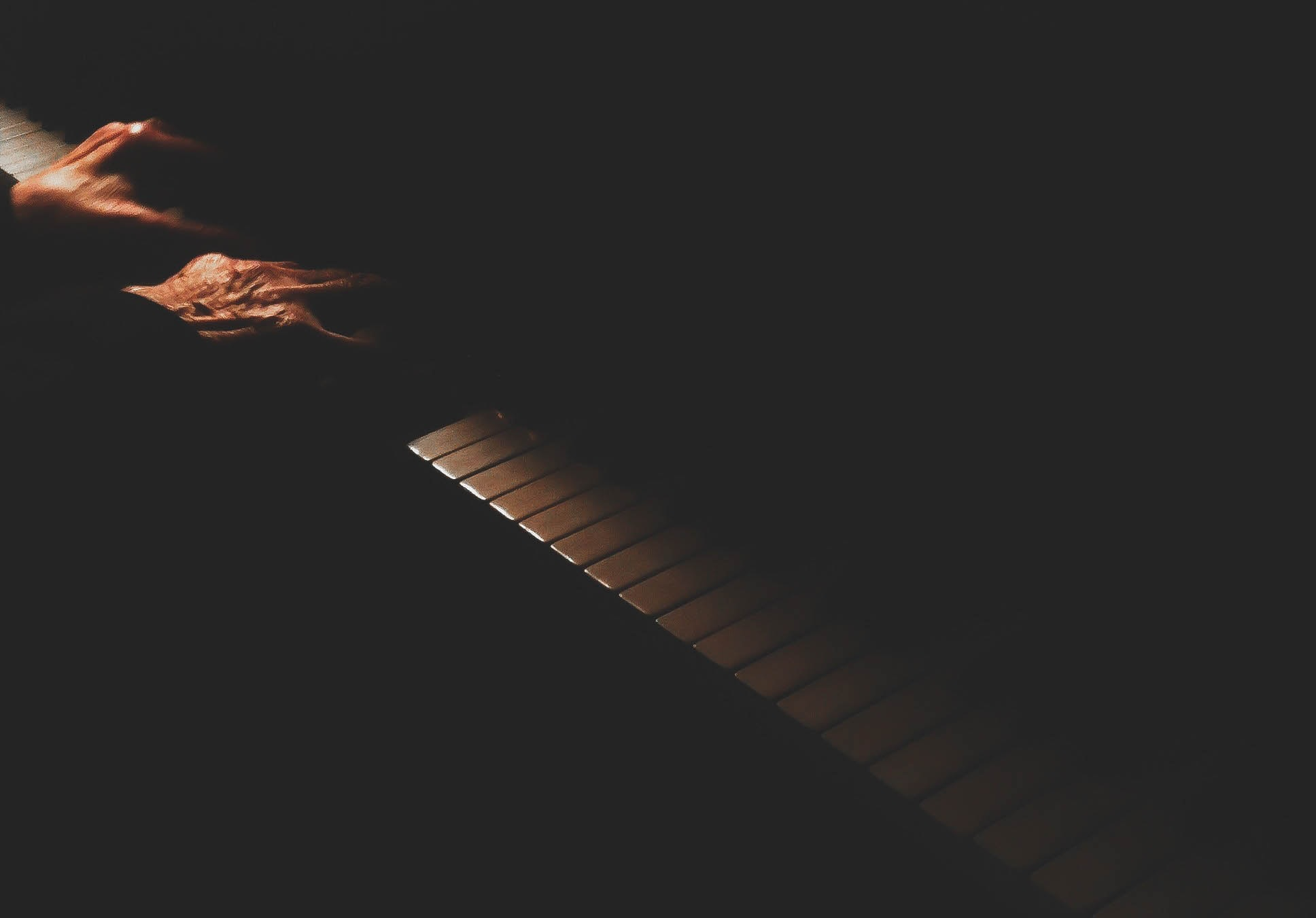 A dim shot of an elderly person's hands on a piano keyboard